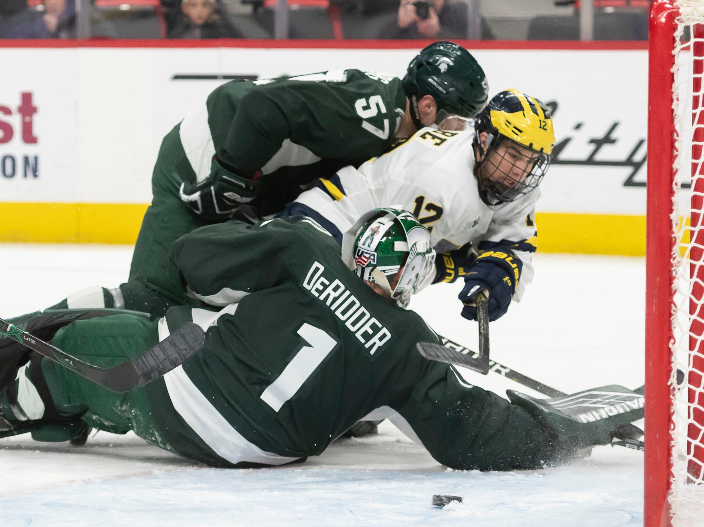 Michigan forward Dakota Raabe tries to get the puck past Michigan State defenseman Jerad Rosburg and goaltender Drew DeRidder in the first period.