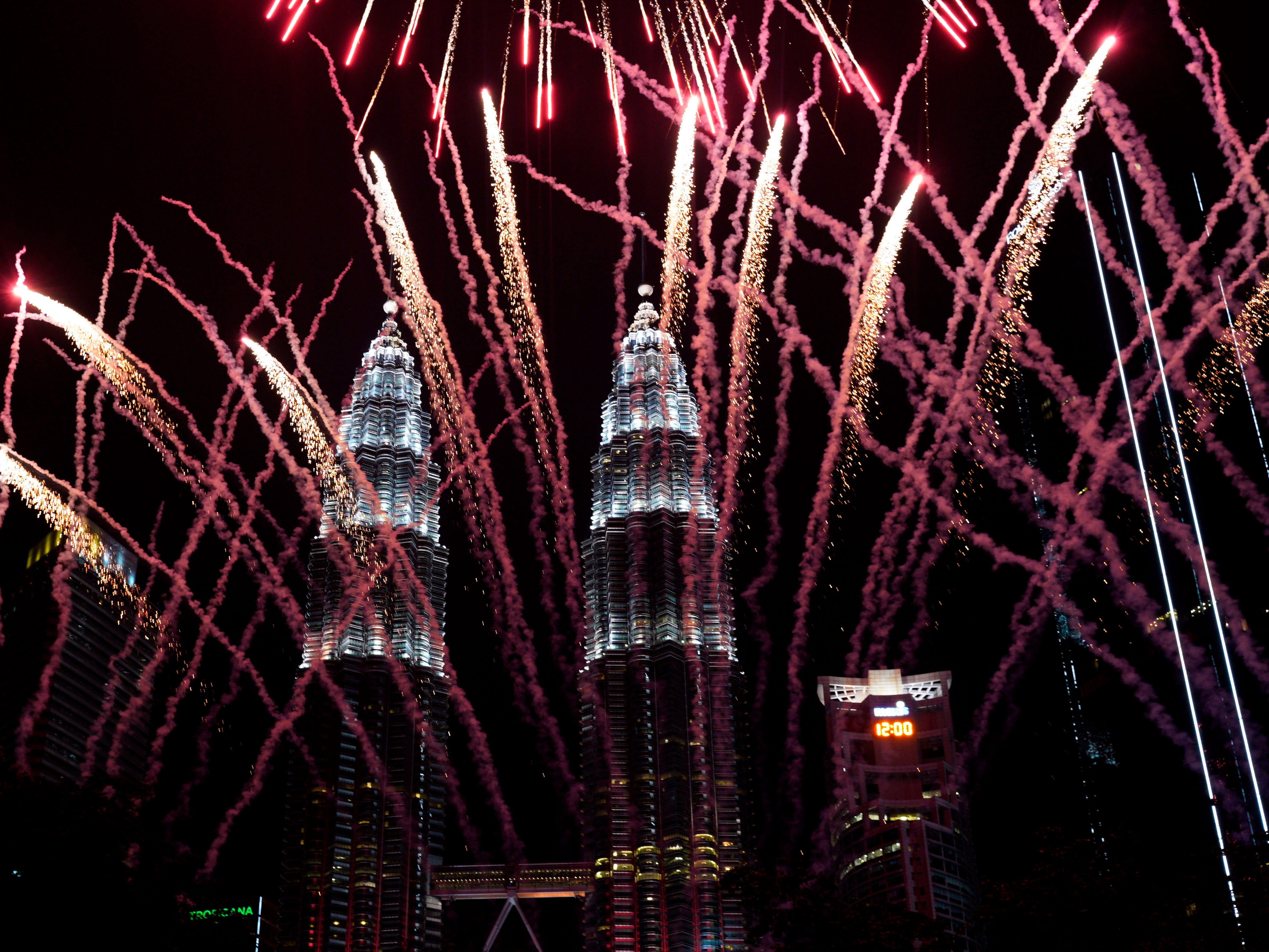 Fireworks explode in front of Malaysia's landmark building, the Petronas Twin Towers, during New Year's celebrations in Kuala Lumpur, Malaysia, on Jan. 1, 2019.