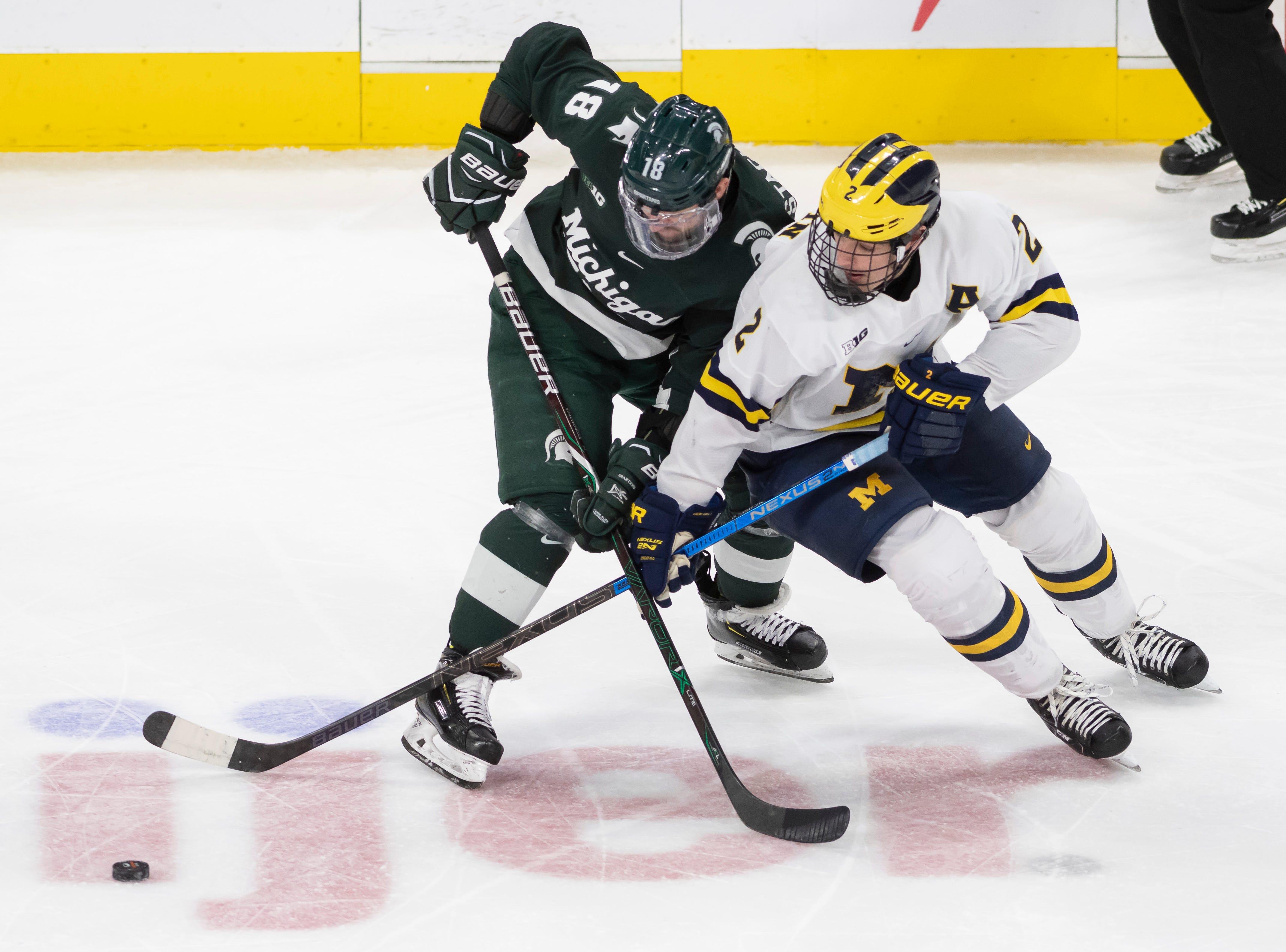 Michigan State forward Wojciech Stachowiak  and Michigan defenseman Luke Martin battle for the puck in the third period.