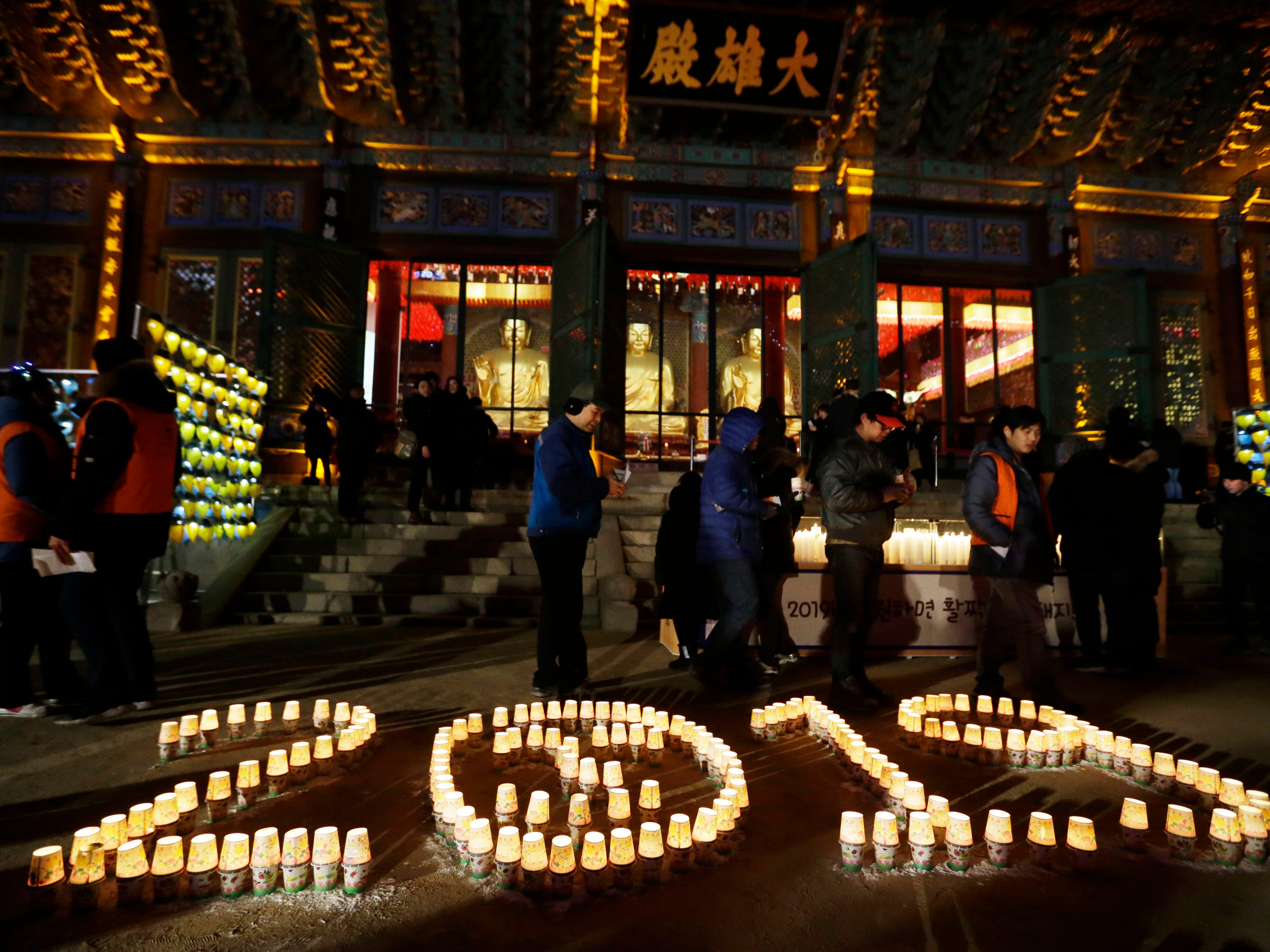 Buddhists light candles during New Year's celebrations at Jogyesa Buddhist temple in Seoul, South Korea, on Jan. 1, 2019.