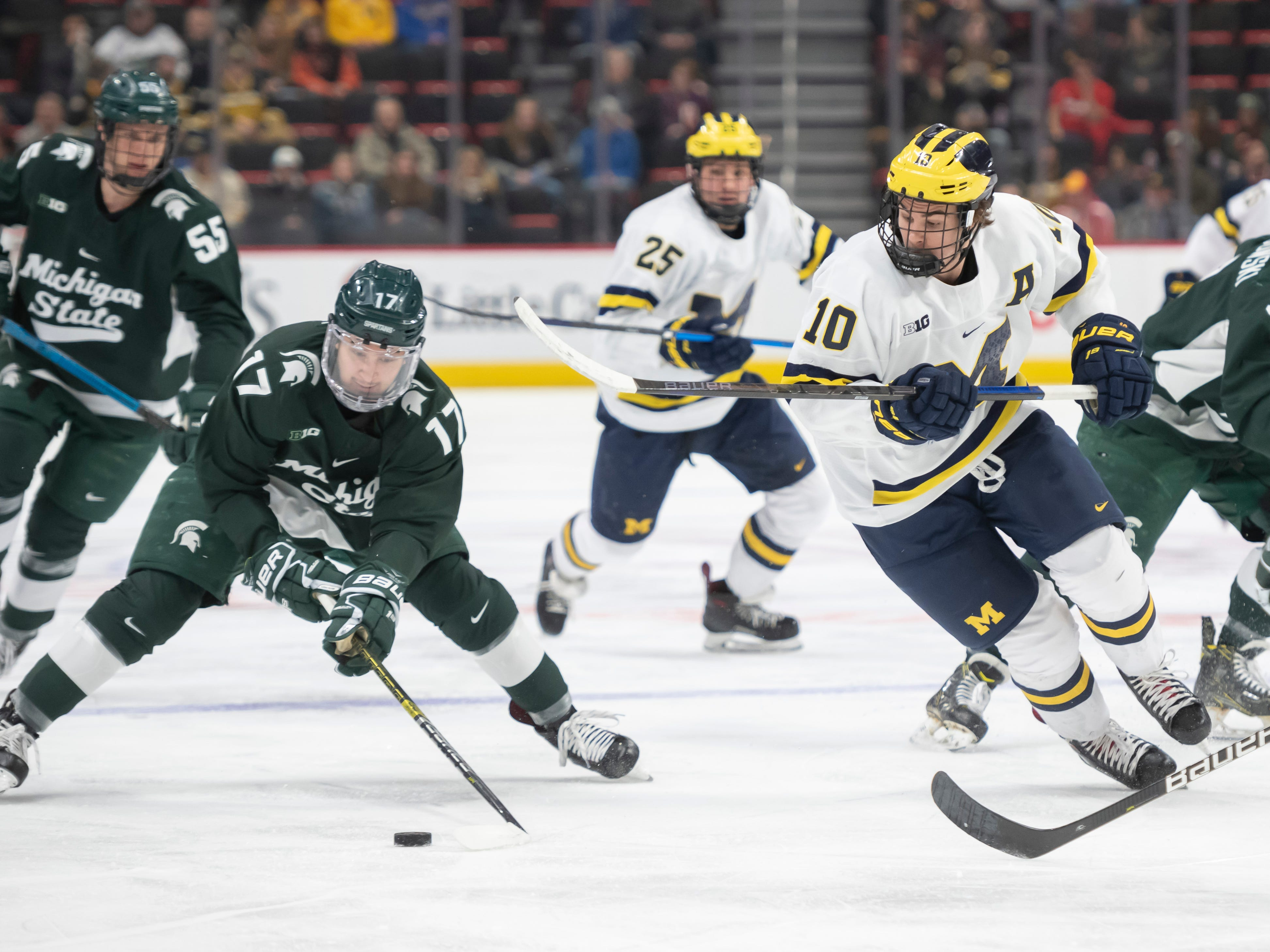 Michigan State forward Taro Hirose tries to keep the puck away from Michigan forward Will Lockwood in the first period.