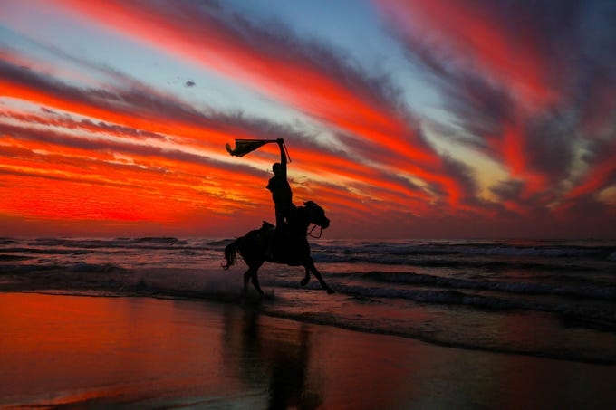 A Palestinian horseman rides on the beach at sunset a few hours prior to the new year's celebrations, west of in Gaza city on Dec. 31, 2018.