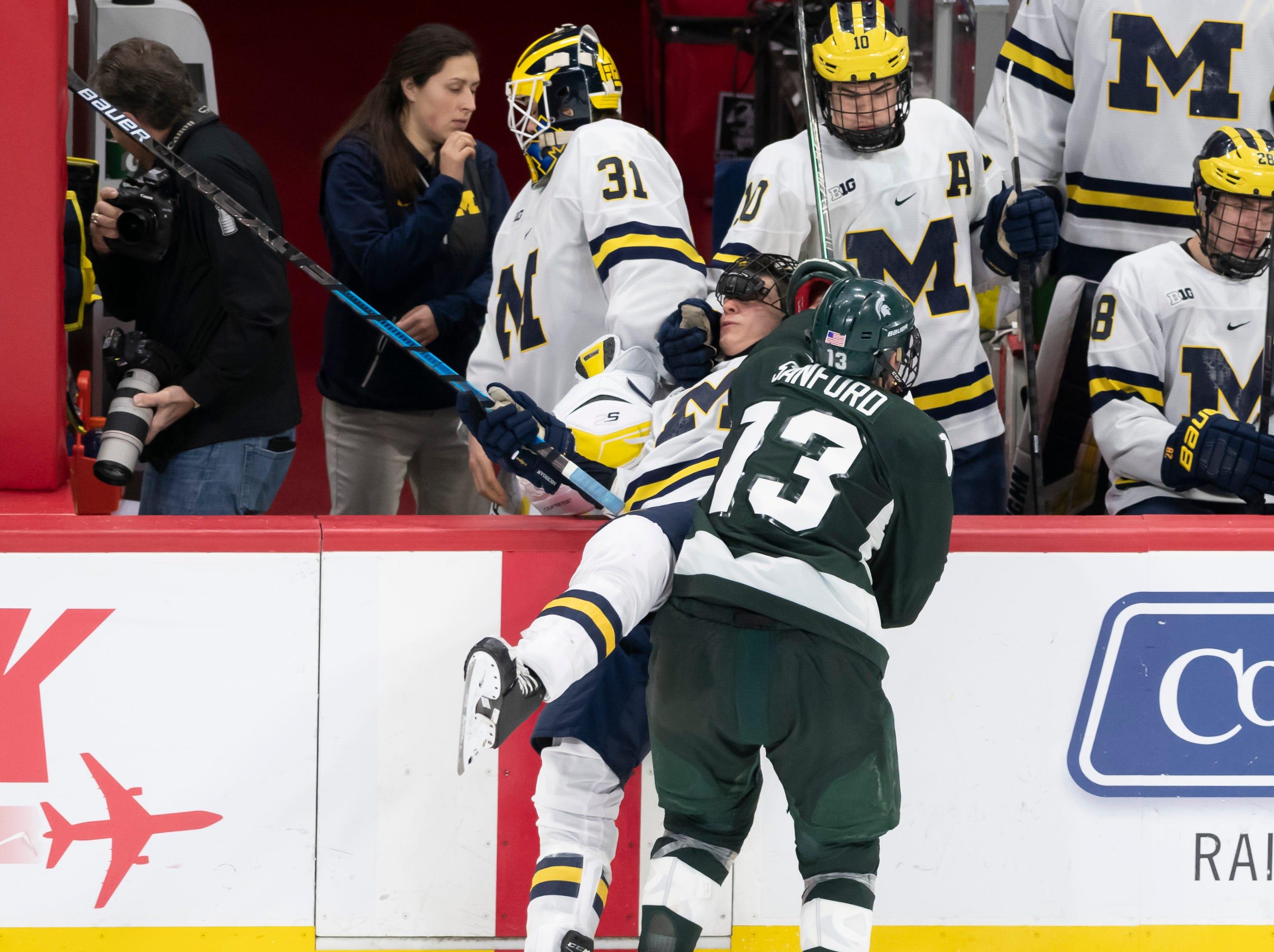 Michigan State forward Brennan Sanford checks Michigan defenseman Joseph Cecconi into the boards in the third period.