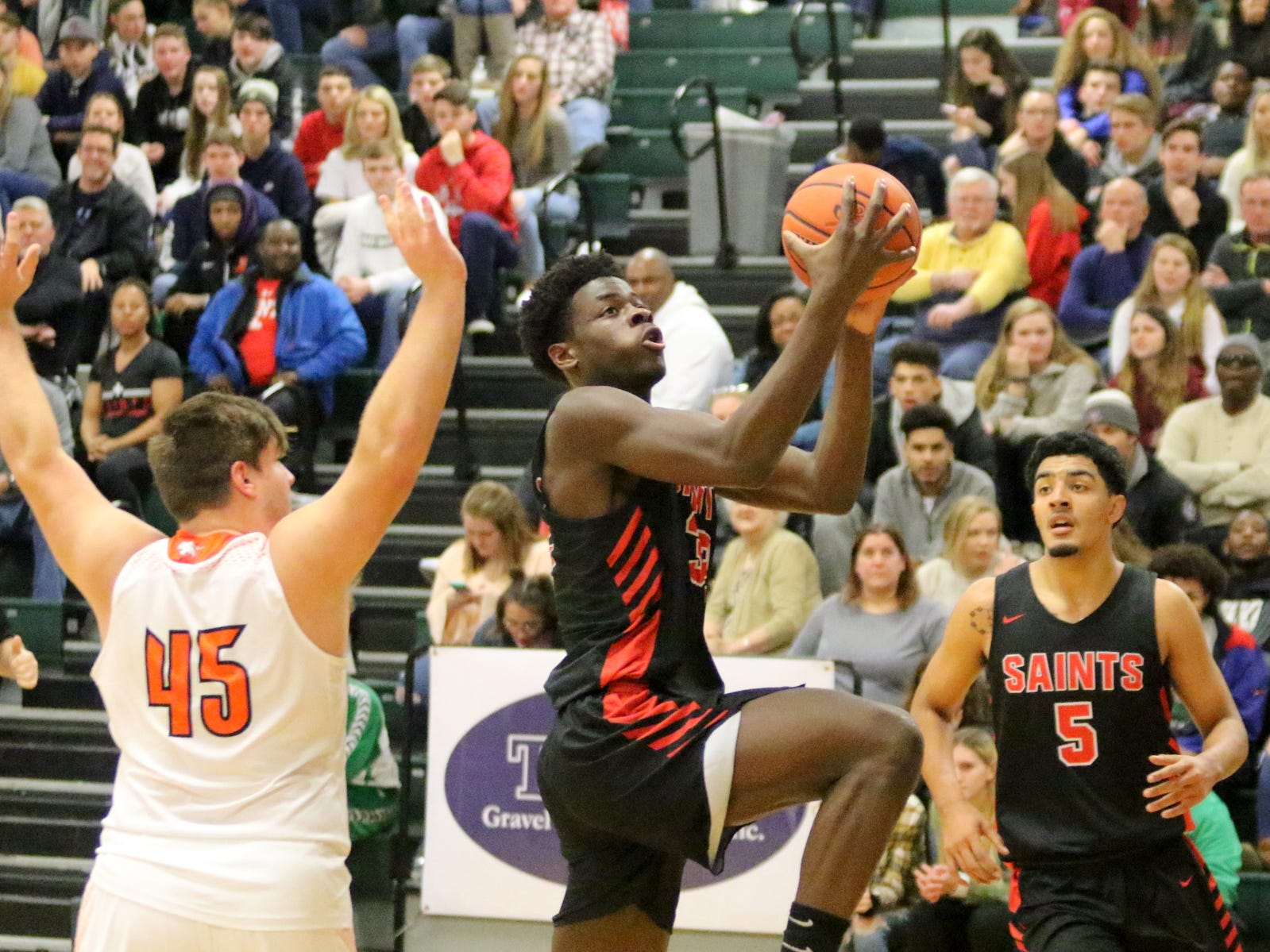 Charles Thompson of St. Stephens/St. Agnes drives in for a layup as Trent Holler defends in the National Division championship game of the Josh Palmer Fund Elmira Holiday Inn Classic on Dec. 30, 2018 at Elmira High School.