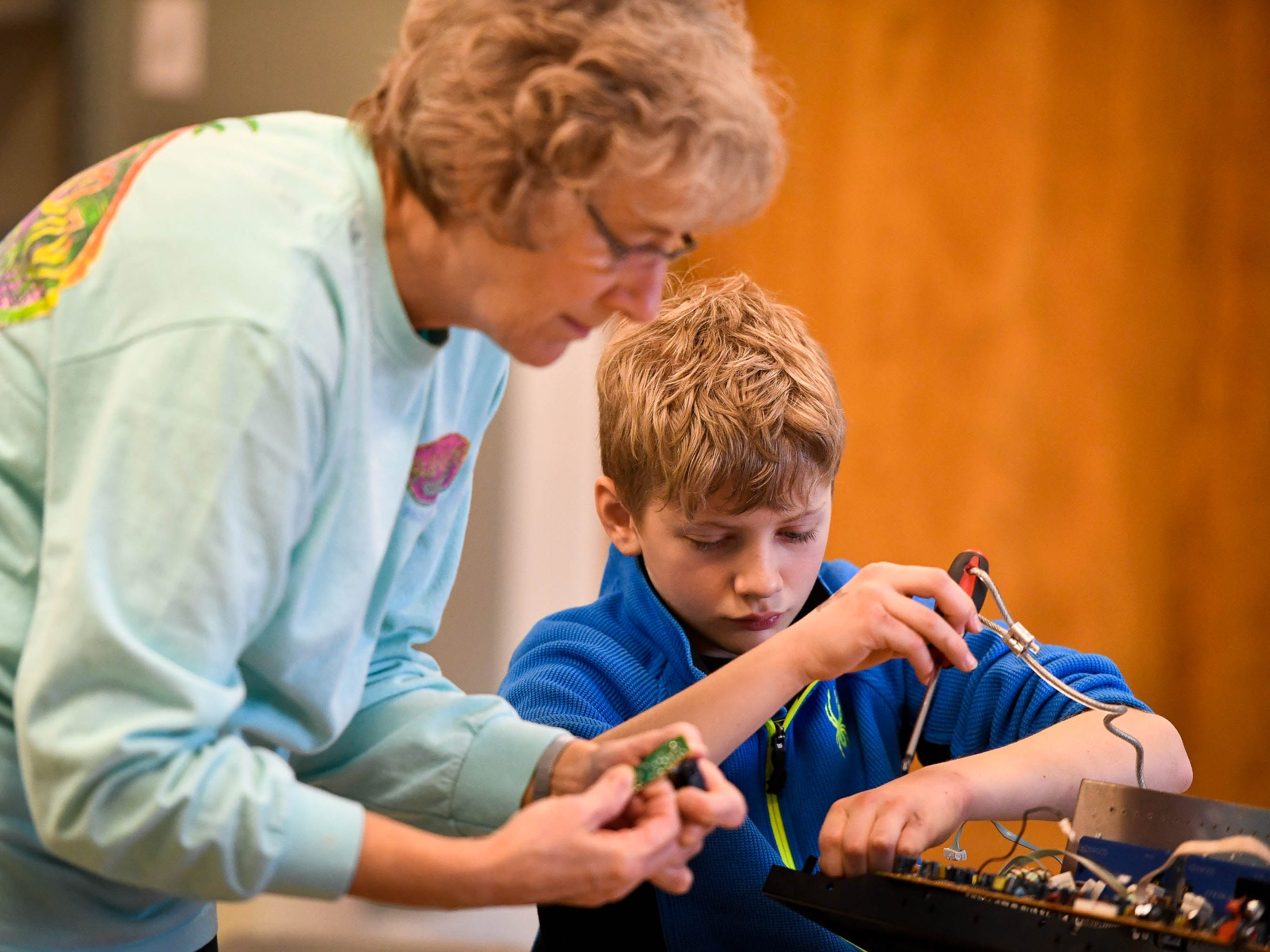 "Xander Calvert, 11 years-old, disassembles electronic equipment with help from his grandmother Kathy Harrison as the pair waits for the noon ""Ball Drop"" celebrating the New Year at the Koch Family Children's Museum of Evansville Monday, December 31, 2018."