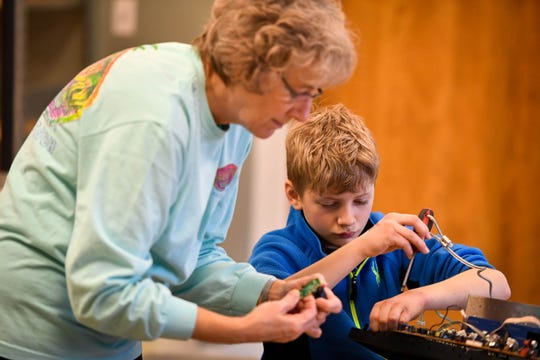 """Xander Calvert, 11 years-old, disassembles electronic equipment with help from his grandmother Kathy Harrison as the pair waits for the noon """"Ball Drop"""" celebrating the New Year at the Koch Family Children's Museum of Evansville Monday, December 31, 2018."""
