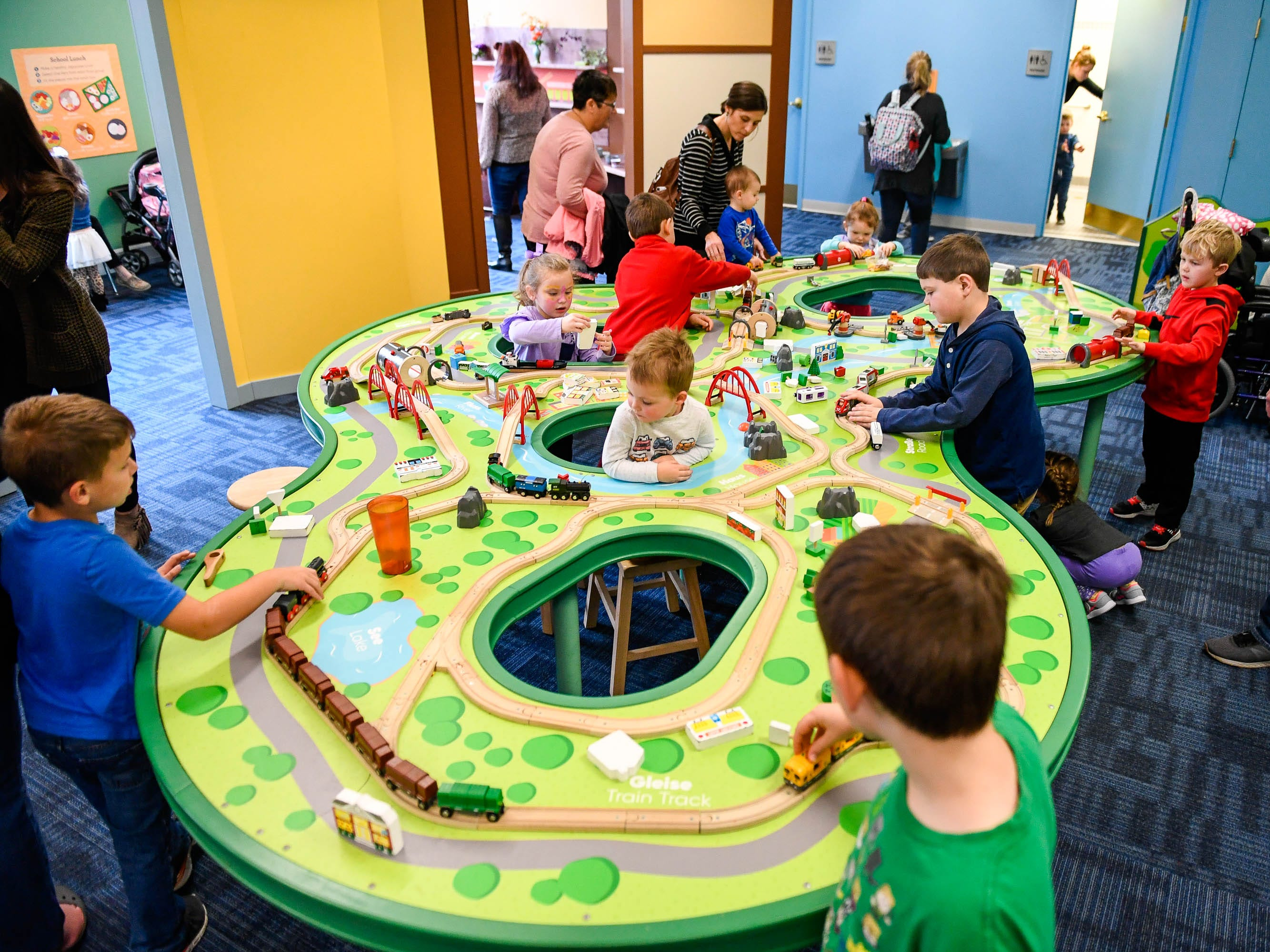 "Kids riding the rails as they play with a train set before the annual noon ""Ball Drop"" celebrating the New Year at the Koch Family Children's Museum of Evansville Monday, December 31, 2018."