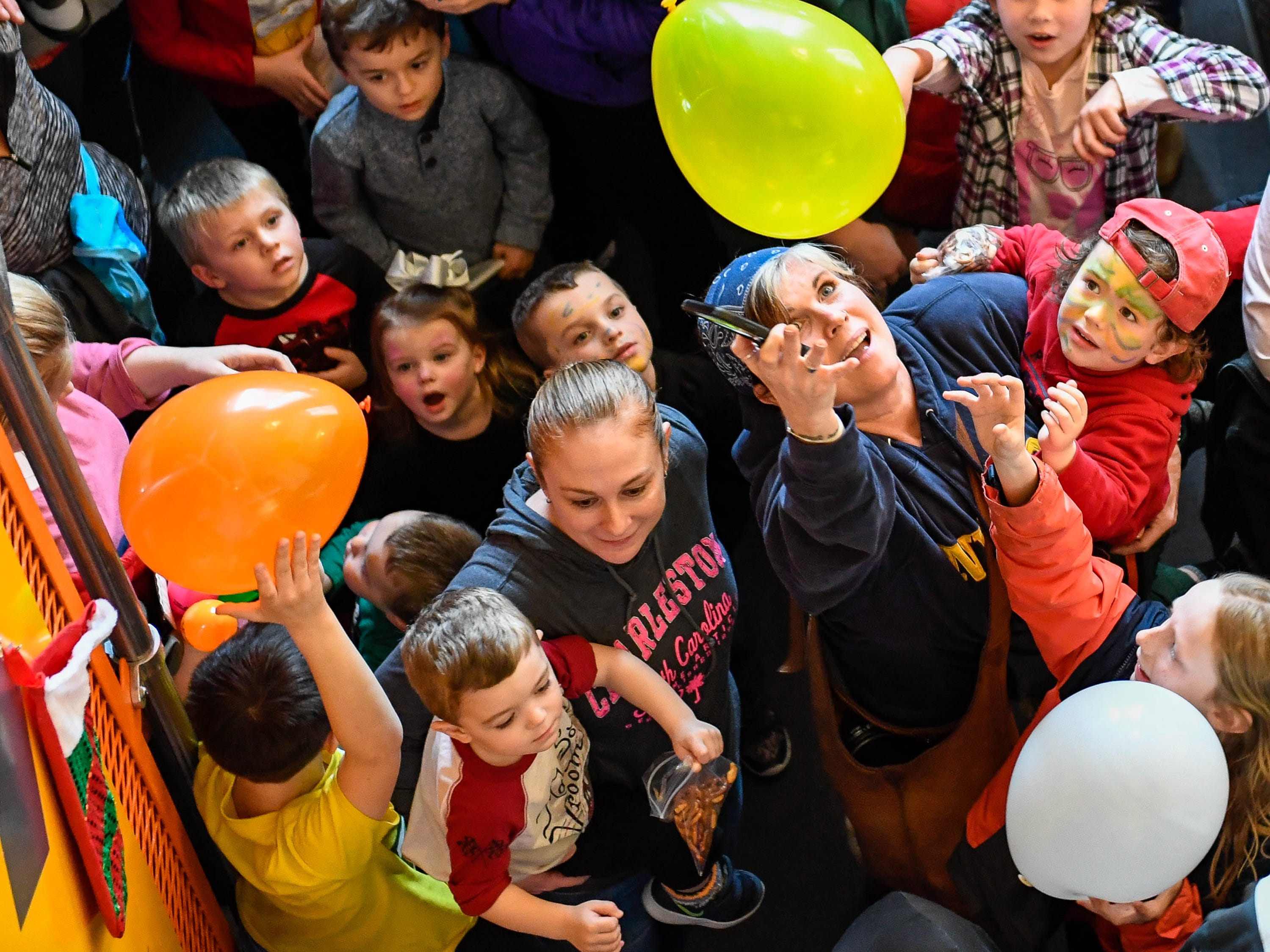 "Children and parents scramble to catch balloons dropped during the annual Koch Family Children's Museum of Evansville noon ""Ball Drop"" celebrating the New Year Monday, December 31, 2018."