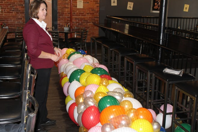 Charlene Wahl, the house manager at The Garrison, looks over balloons Monday at the restaurant. The Garrison was one of several downtown Fremont establishments preparing for New Year's Eve activities.