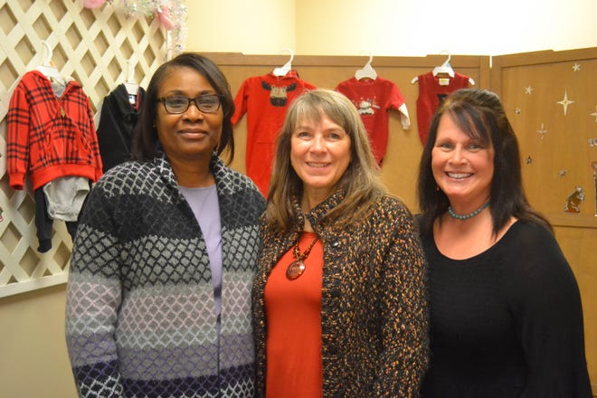 Heartbeat of Ottawa County staff include, from left, Yvette Rash, client services; Executive Director Kim Perkins, and Marketing Specialist Sandy Hymore. The women are surrounded by a few of the baby outfits that are available, along with other infant supplies, to young parents who use Heartbeat services.