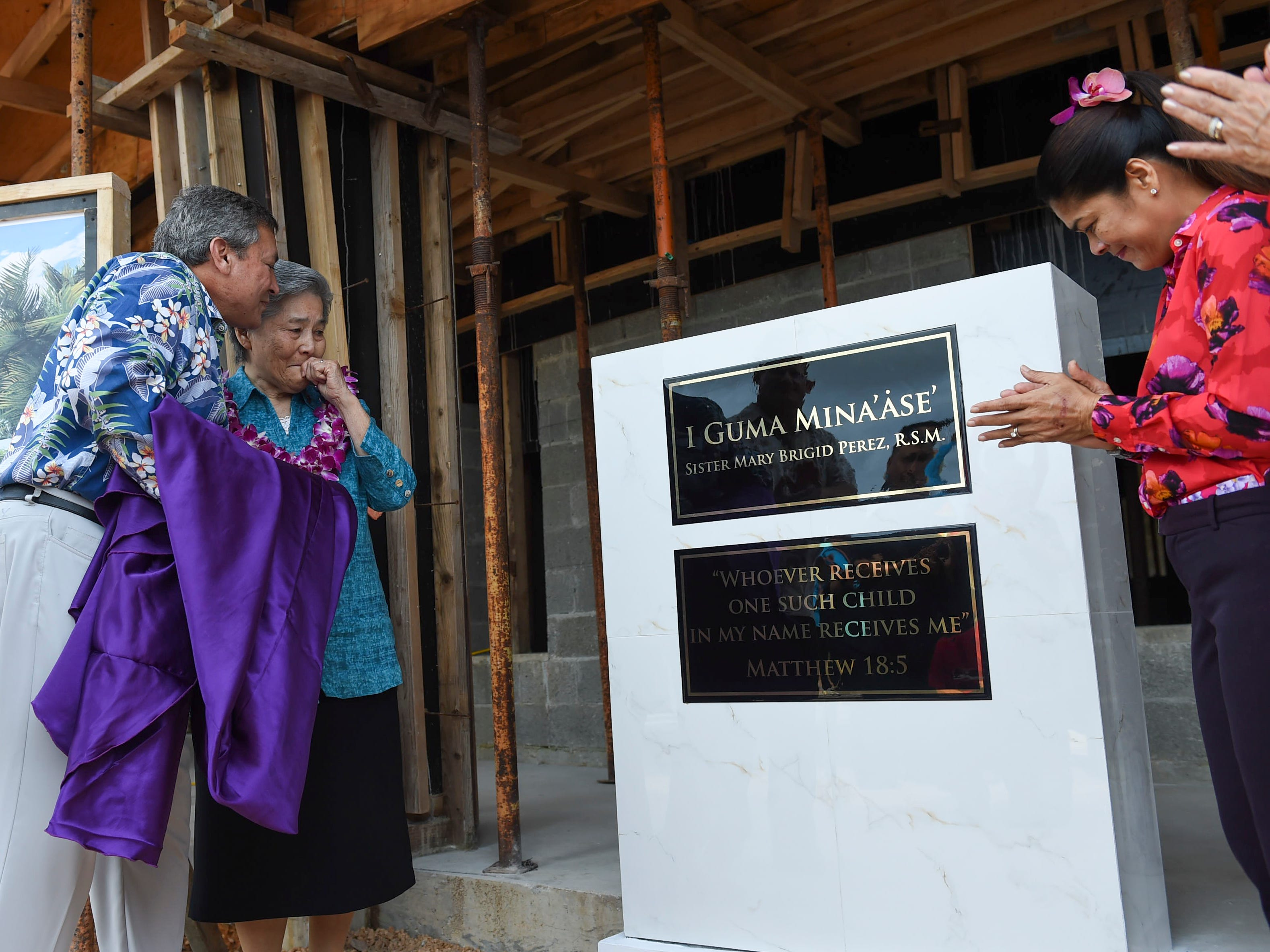 Gov. Eddie Baza Calvo congratulates Sister Mary Brigid Perez after unveiling a dedication plaque at the contruction site of the newly named I Guma Mina'åse Sister Mary Brigid Perez, R.S.M. in Barrigada on Dec. 31, 2018.