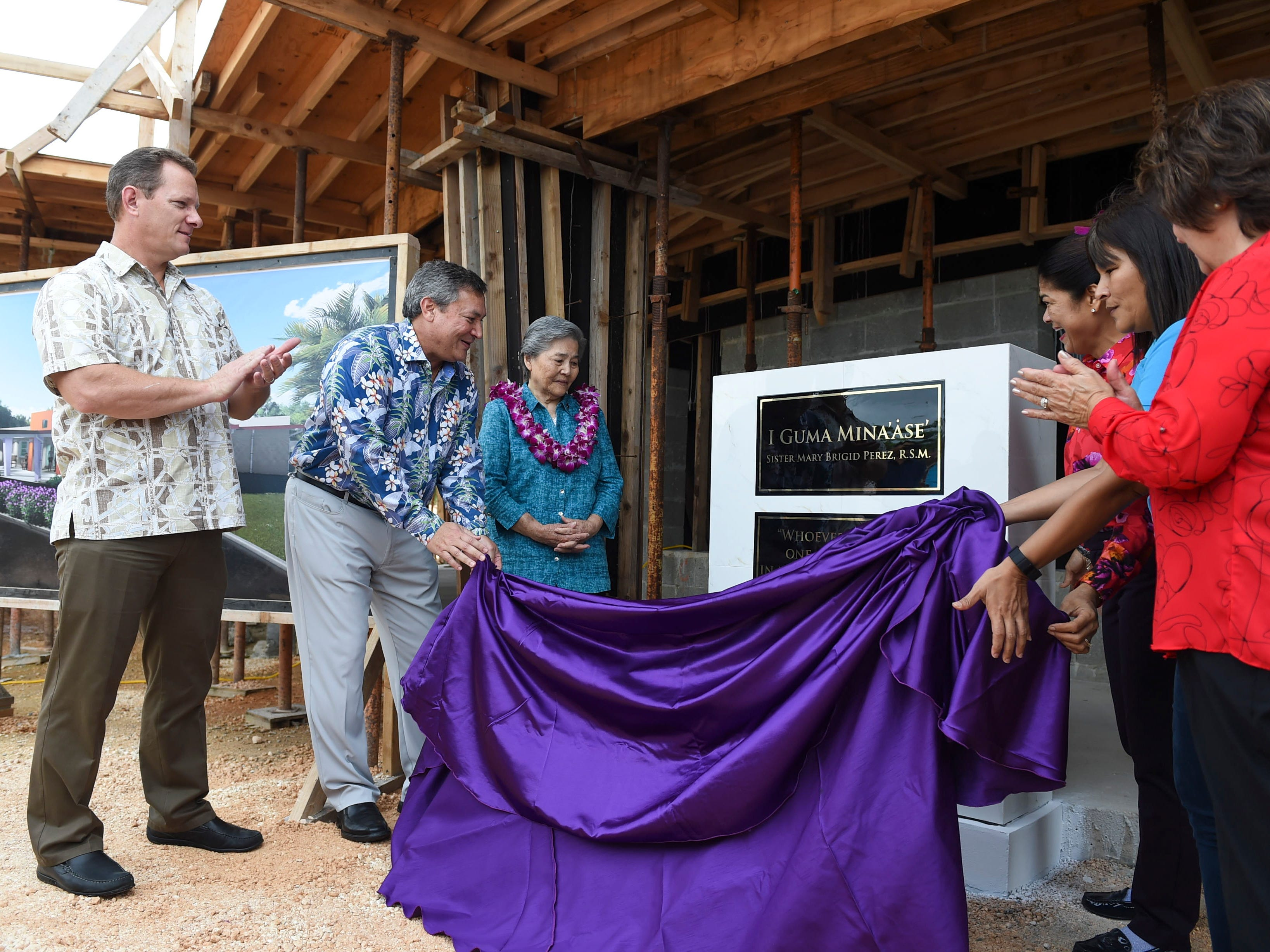 Dignitaries unveil a plaque dedicated to Sister Mary Brigid Perez, center, during a dedication ceremony for the redesignation of the former Rigålu House to I Guma Mina'åse' Sister Mary Brigid Perez, R.S.M. in Barrigada on Dec. 31, 2018.