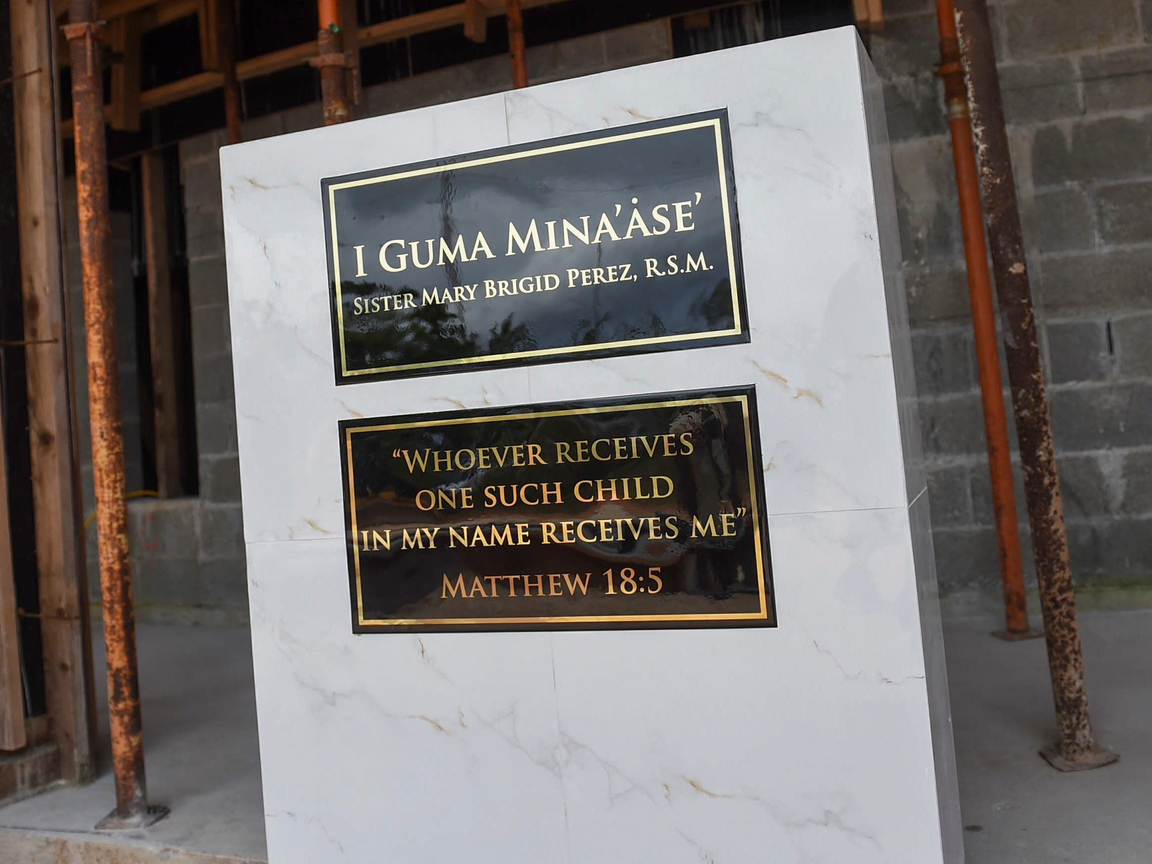 A dedication plaque is unveiled during a ceremony for the redesignation of the former Rigålu House to I Guma Mina'åse' Sister Mary Brigid Perez, R.S.M. in Barrigada on Dec. 31, 2018.
