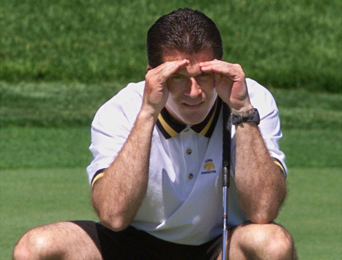 From 1999: New Iowa basketball coach Steve Alford, wearing an Iowa Hawkeyes polo, shades his eyes while checking the lie on a putt during the Variety Club golf outing at Glen Oaks Country Club.