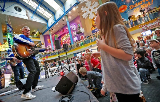 Zak Morgan,  left, and his group perform at the Countdown to noon celebration at the Children's Museum of Indianapolis, Monday, Dec. 31, 2018. Ella Skinner, right, joins the fun.