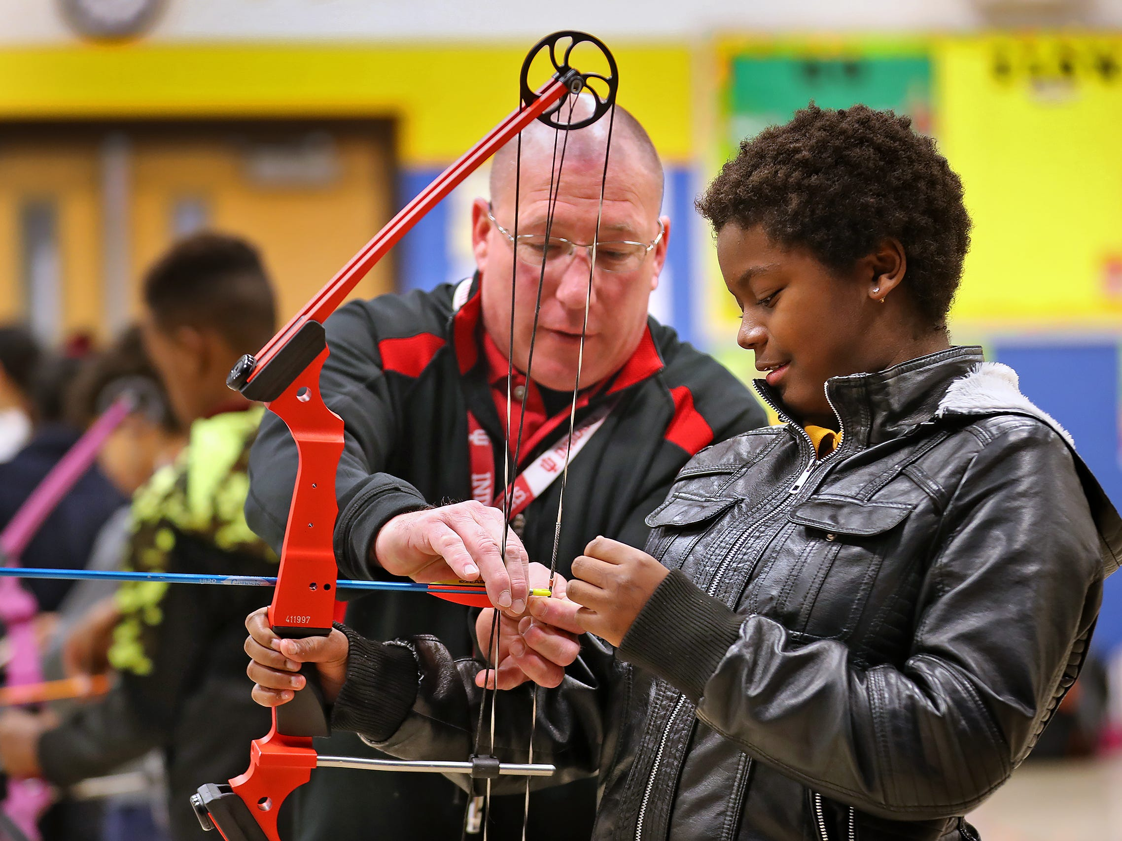 William Crawford, left, gives instruction to Nikita Barnes during archery class at Lew Wallace Elementary IPS 107, Thursday, Dec. 20, 2018.