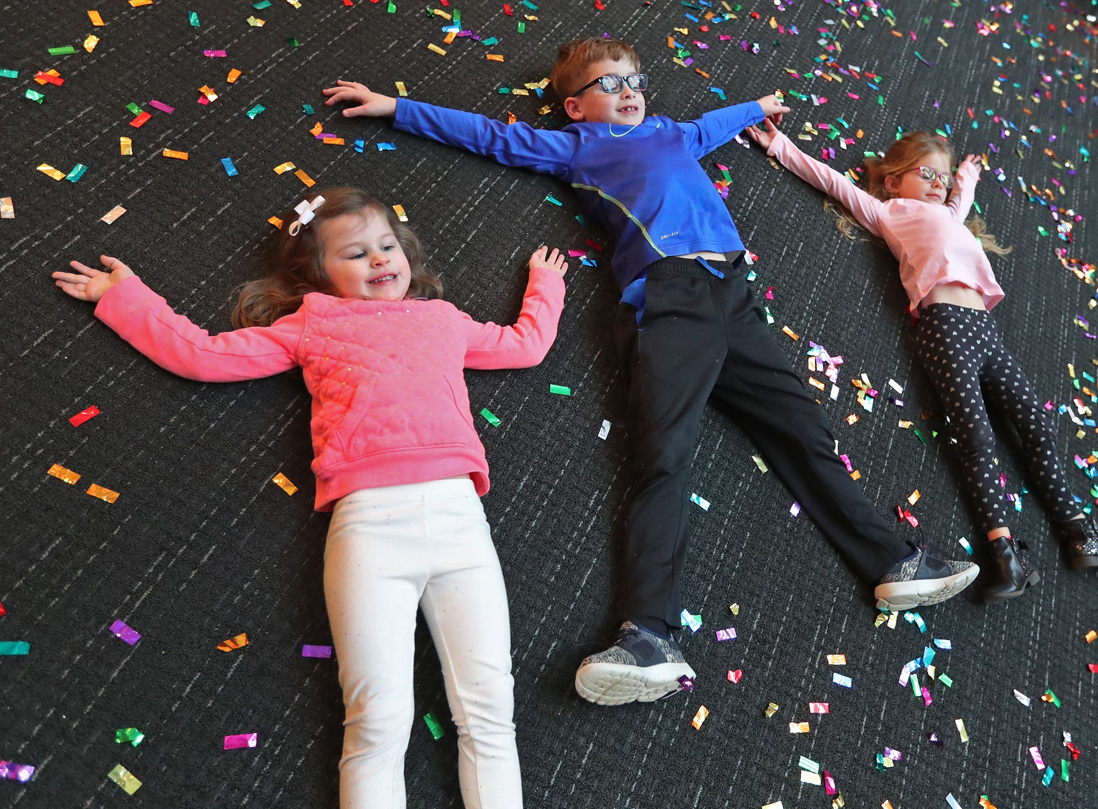 Hayden Soultz, from left, Easton Pedigo, and Cora Pedigo do snow angels and pose for photos in the confetti dropped at noon, at the Countdown to noon celebration at the Children's Museum of Indianapolis, Monday, Dec. 31, 2018.