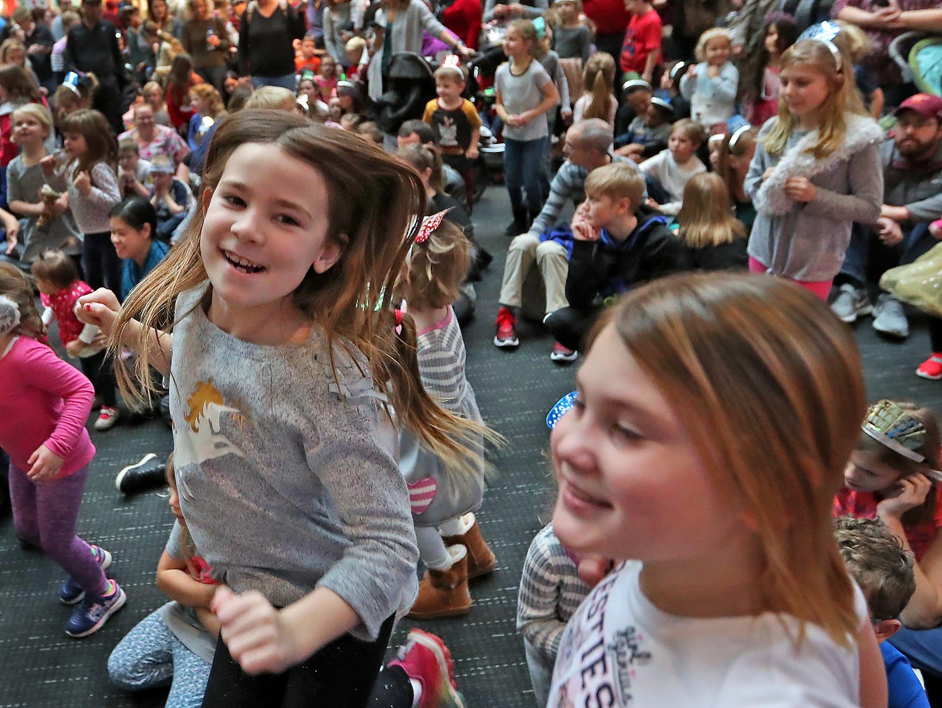 Ella Skinner, left, and Katie Jacobs join others in dancing as the Zak Morgan group performs at the Countdown to noon celebration at the Children's Museum of Indianapolis, Monday, Dec. 31, 2018.