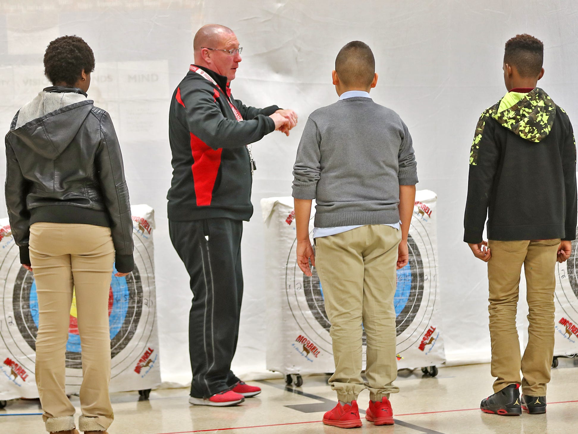 William Crawford gives instruction on picking up arrows that sixth graders shot during archery class at Lew Wallace Elementary IPS 107, Thursday, Dec. 20, 2018.