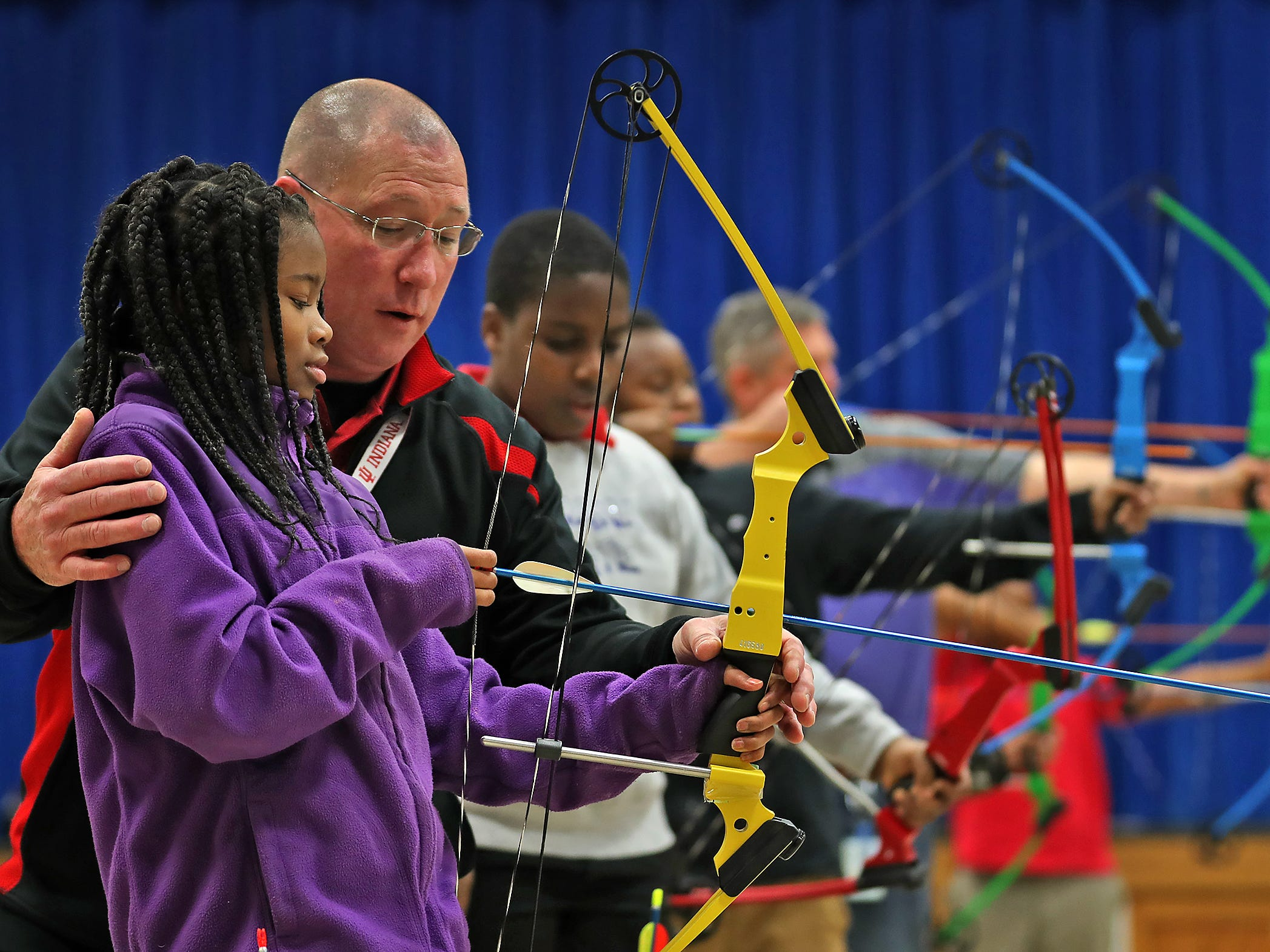 William Crawford, right, gives shooting tips to Brianna Smith during archery class at Lew Wallace Elementary IPS 107, Thursday, Dec. 20, 2018.