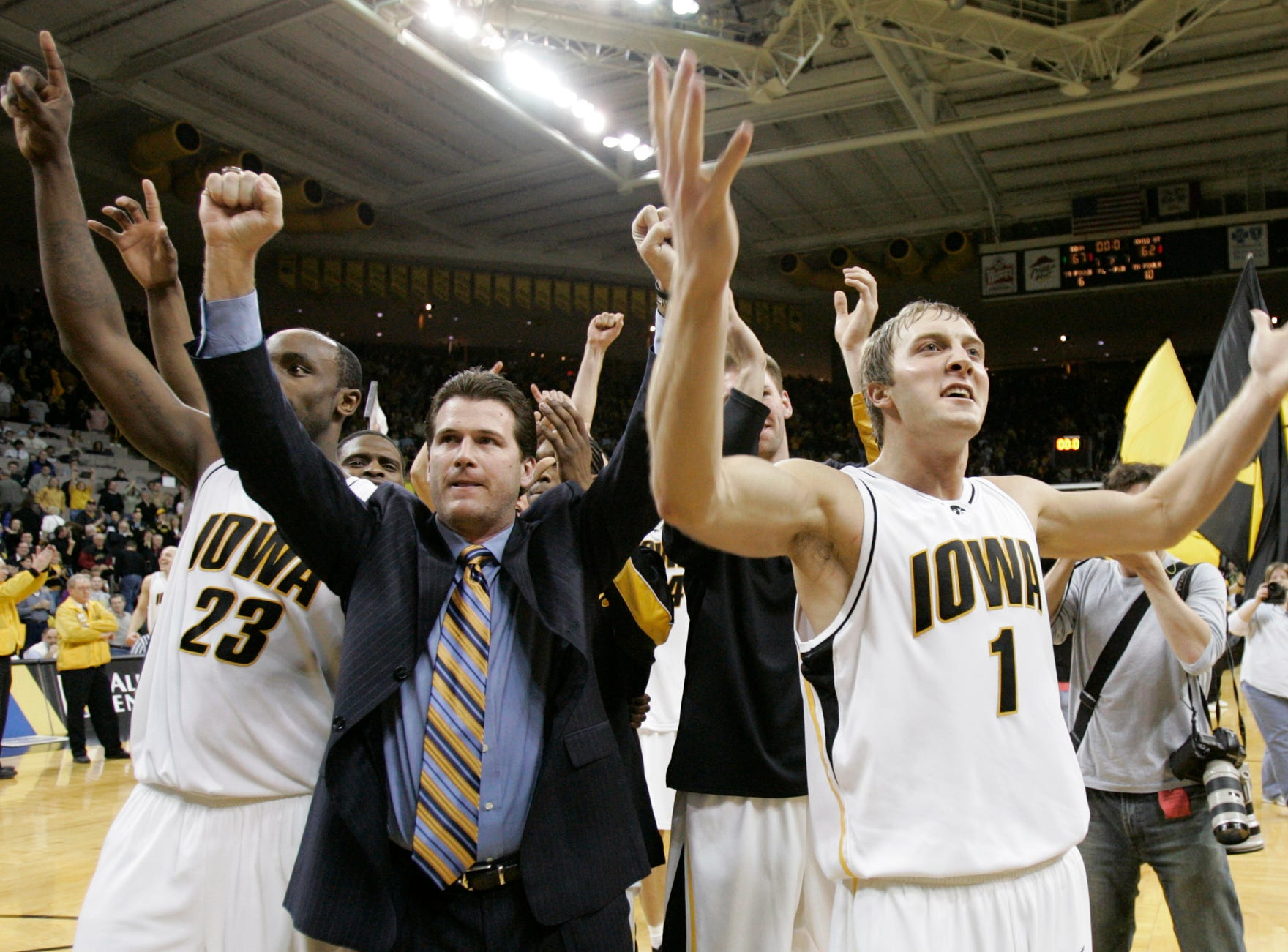 Iowa coach Steve Alford, second from left,  celebrates with his players Doug Thomas, left, and Adam Haluska, right, after their 67-62 win over Ohio State in this NCAA college basketball game, Saturday, Jan. 28, 2006, in Iowa City, Iowa.  Haluska scored 18 points to lead Iowa in the win.