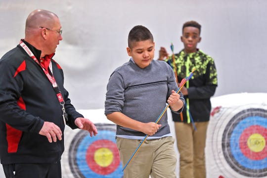 William Crawford, left, talks with student Francisco Barraza as he retrieves his arrows and returns to the shooting line, during archery class at Lew Wallace Elementary IPS 107, Thursday, Dec. 20, 2018.