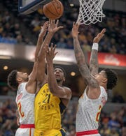 Thaddeus Young of the Indiana Pacers goes up for a shot as he is defended by Tyler Dorsey of the Atlanta Hawks (left) and John Collins at Bankers Life Fieldhouse, Indianapolis, Tuesday, Dec. 31, 2018. Indiana beat Atlanta 116-108.