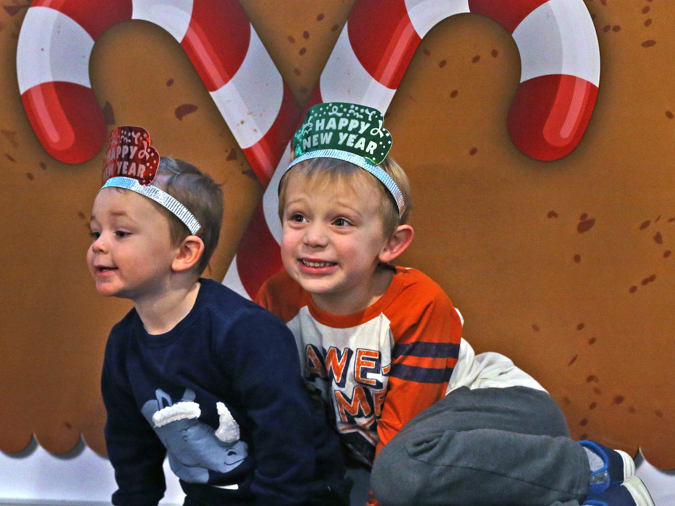 Ellis, left, and Gibson Binder pose by a holiday mural for photos taken by their parents, at the Countdown to noon celebration at the Children's Museum of Indianapolis, Monday, Dec. 31, 2018.