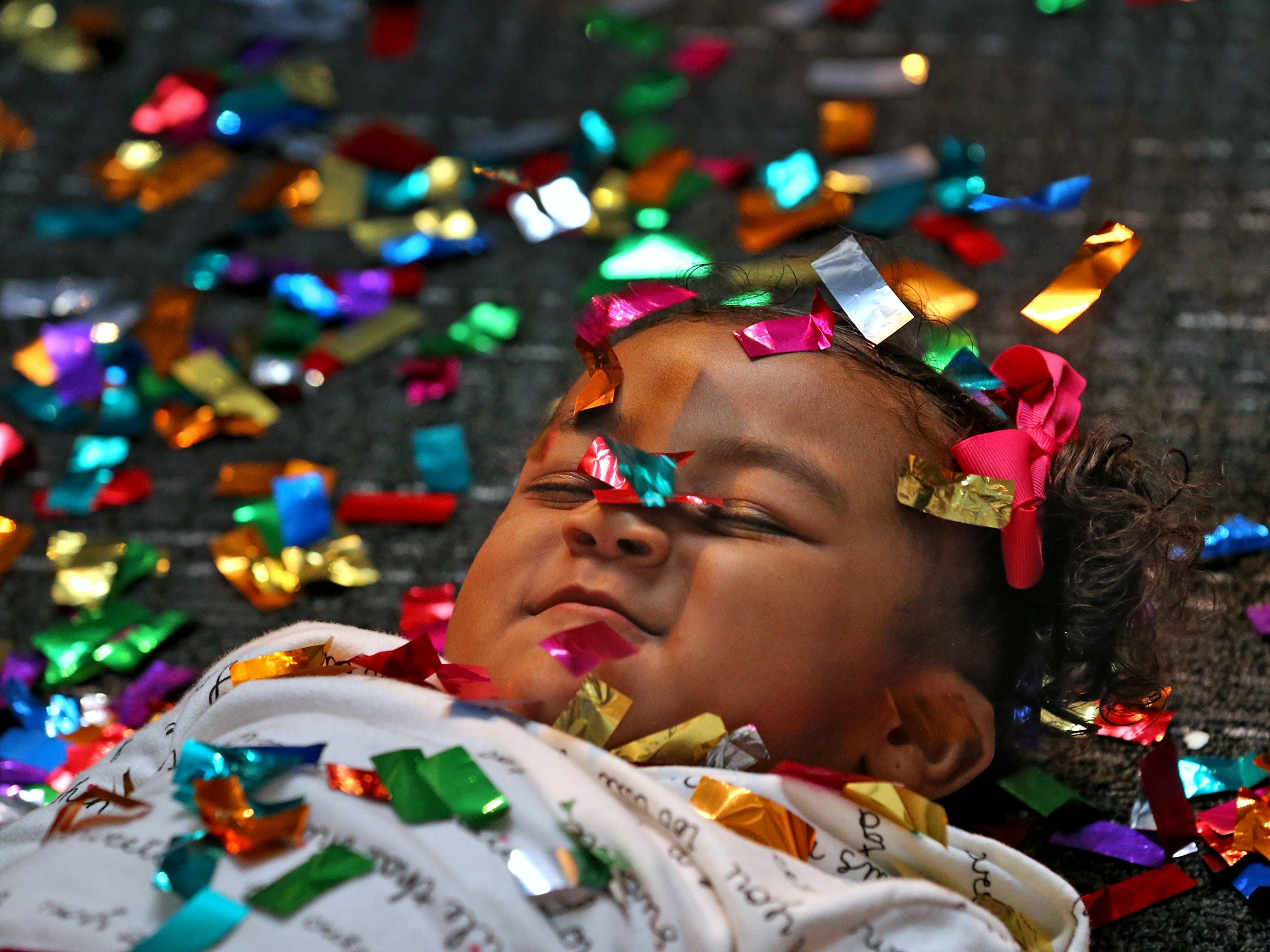 Kyndall Riley smiles while having confetti dropped on her face at the Countdown to noon celebration at the Children's Museum of Indianapolis, Monday, Dec. 31, 2018.