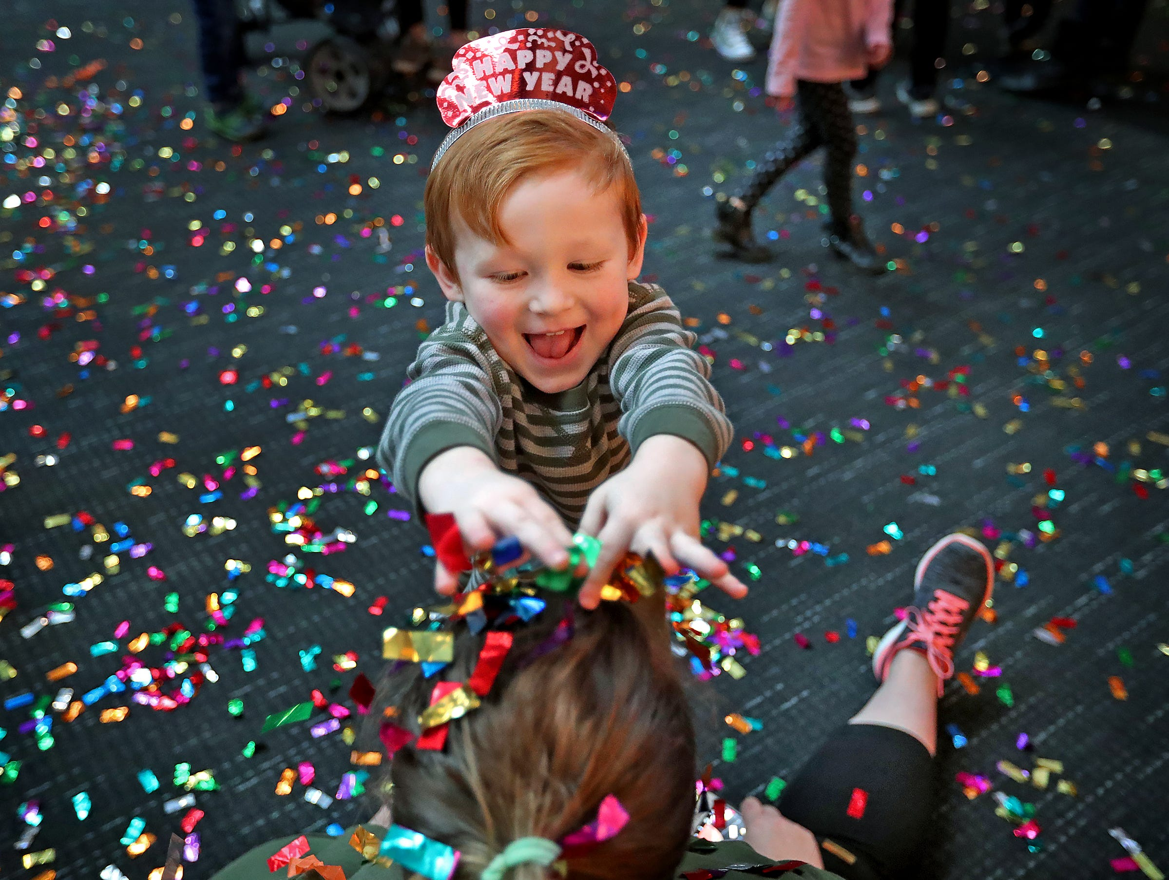 Aaron Lenon puts confetti in his mom, Mindy Beigle's hair, at the Countdown to noon celebration at the Children's Museum of Indianapolis, Monday, Dec. 31, 2018.