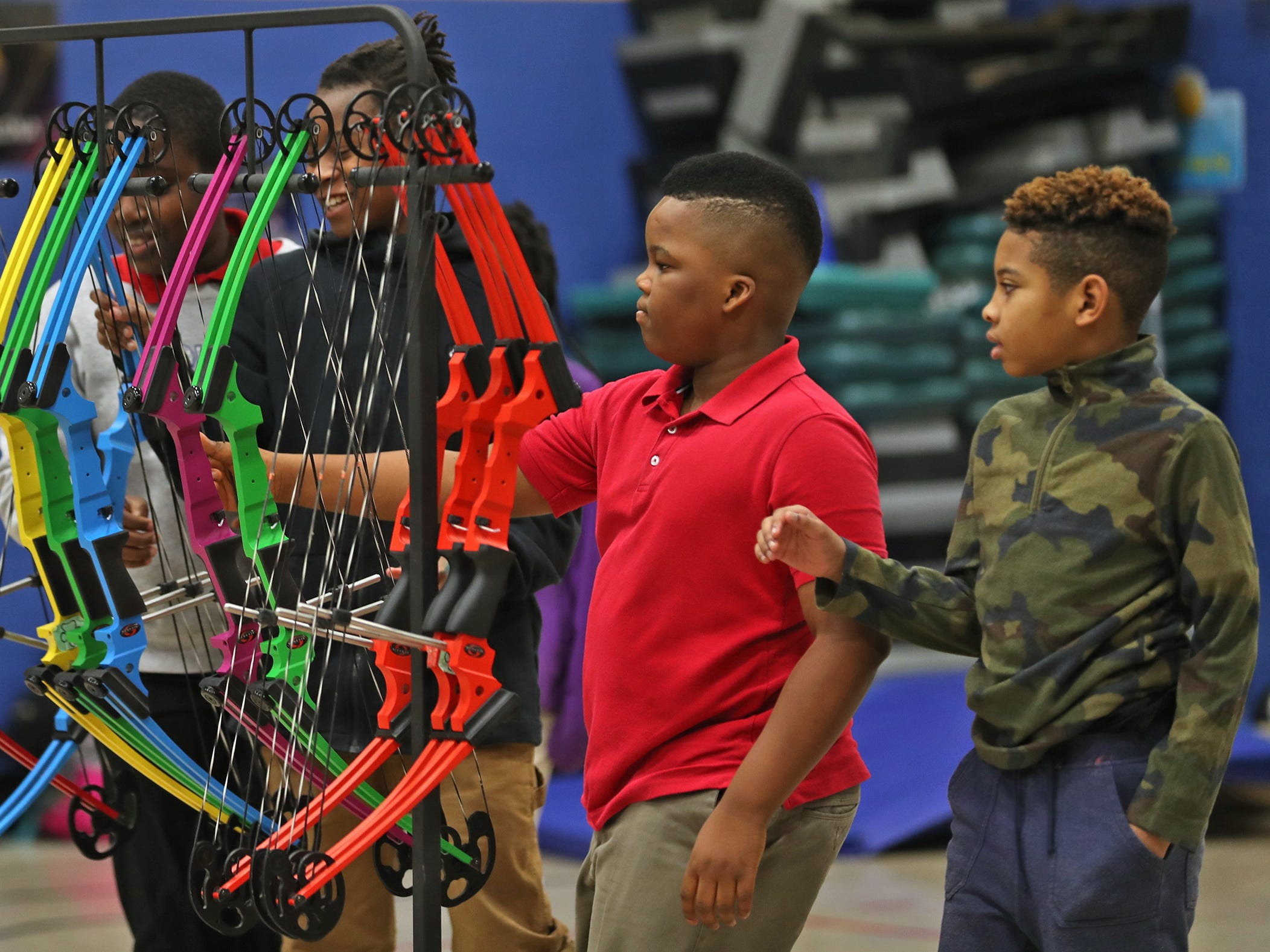 Oluwatunmise Ogbeide, left, and Courtney Washington grab their bows to shoot, during archery class at Lew Wallace Elementary IPS 107, Thursday, Dec. 20, 2018.