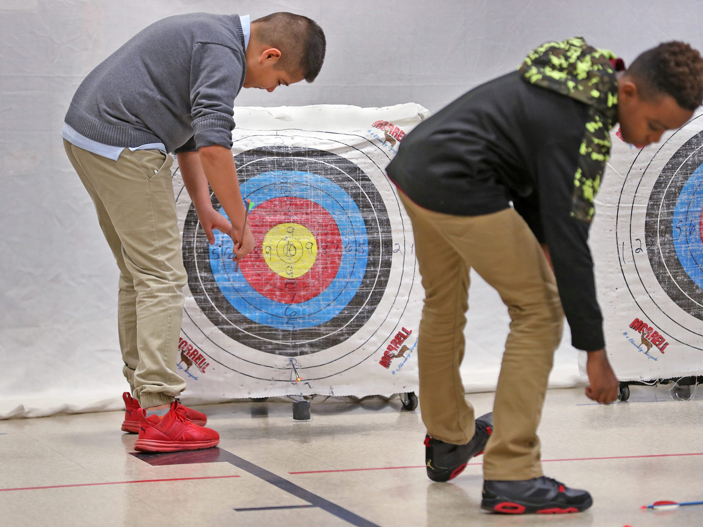 Francisco Barraza, left, and Aadian Richmond retrieve their arrows during archery class at Lew Wallace Elementary IPS 107, Thursday, Dec. 20, 2018.