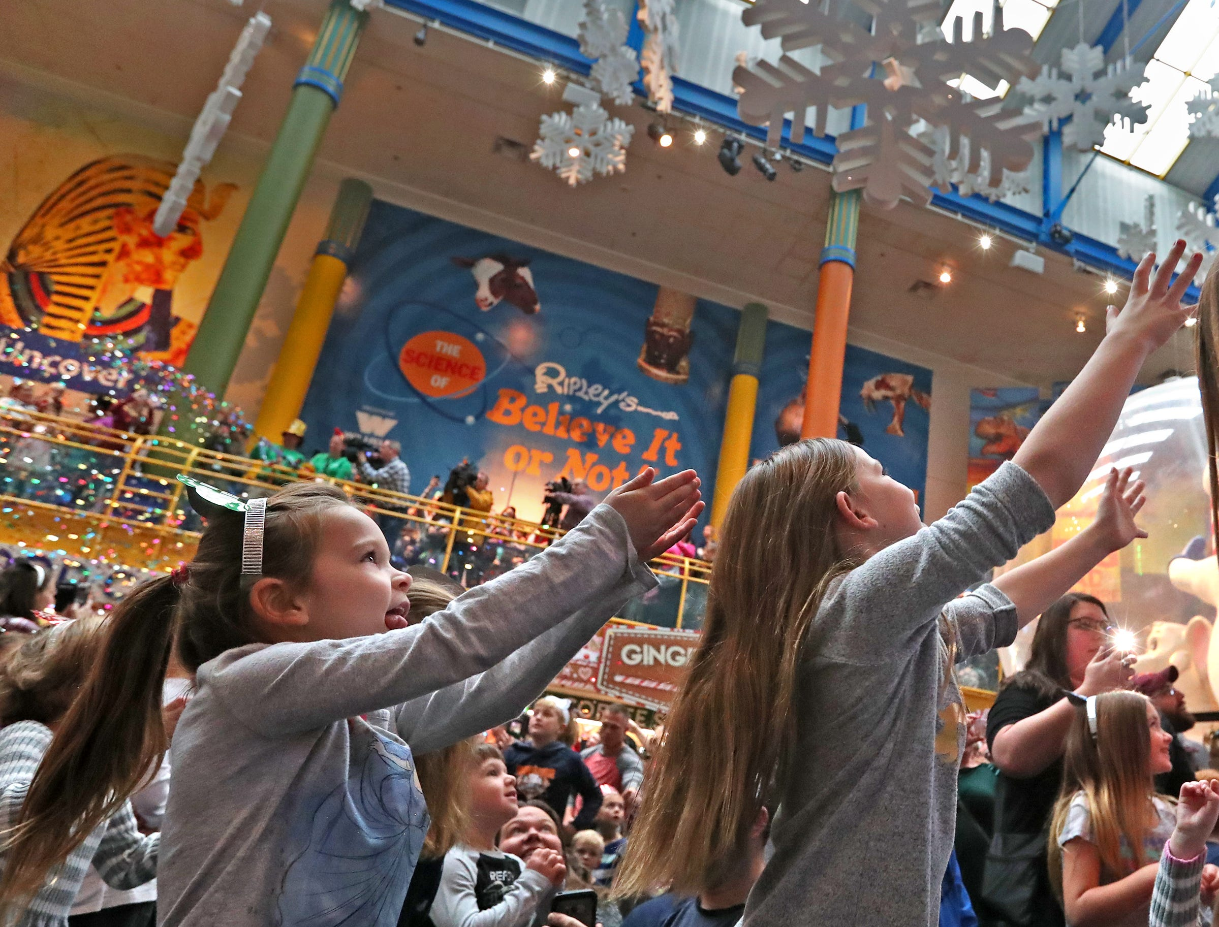 Kids reach for falling confetti at the Countdown to noon celebration at the Children's Museum of Indianapolis, Monday, Dec. 31, 2018.