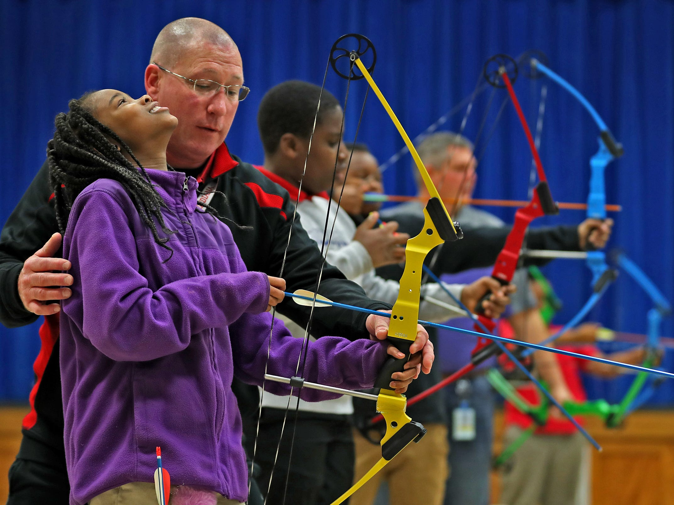 William Crawford helps Brianna Smith with her shooting stance during archery class at Lew Wallace Elementary IPS 107, Thursday, Dec. 20, 2018.