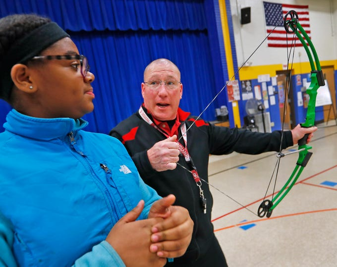 William Crawford, right, gives instruction to Krystal Johnson during archery class at Lew Wallace Elementary IPS 107, Thursday, Dec. 20, 2018.