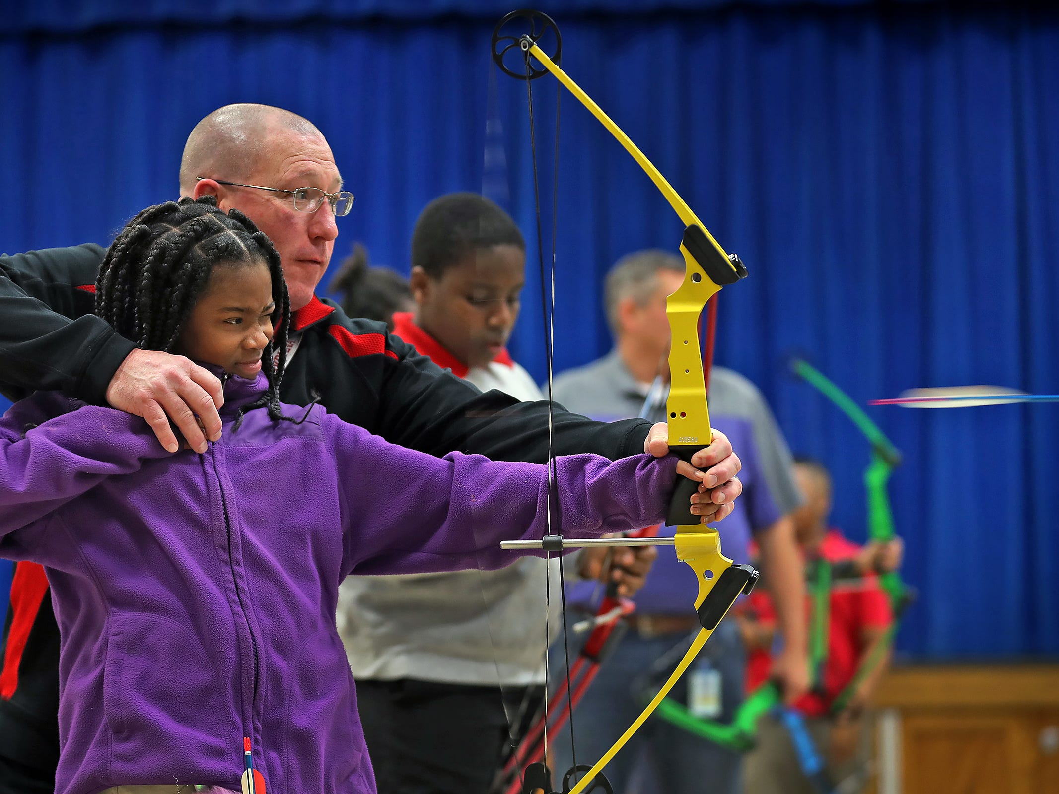 William Crawford helps Brianna Smith shoot during archery class at Lew Wallace Elementary IPS 107, Thursday, Dec. 20, 2018.