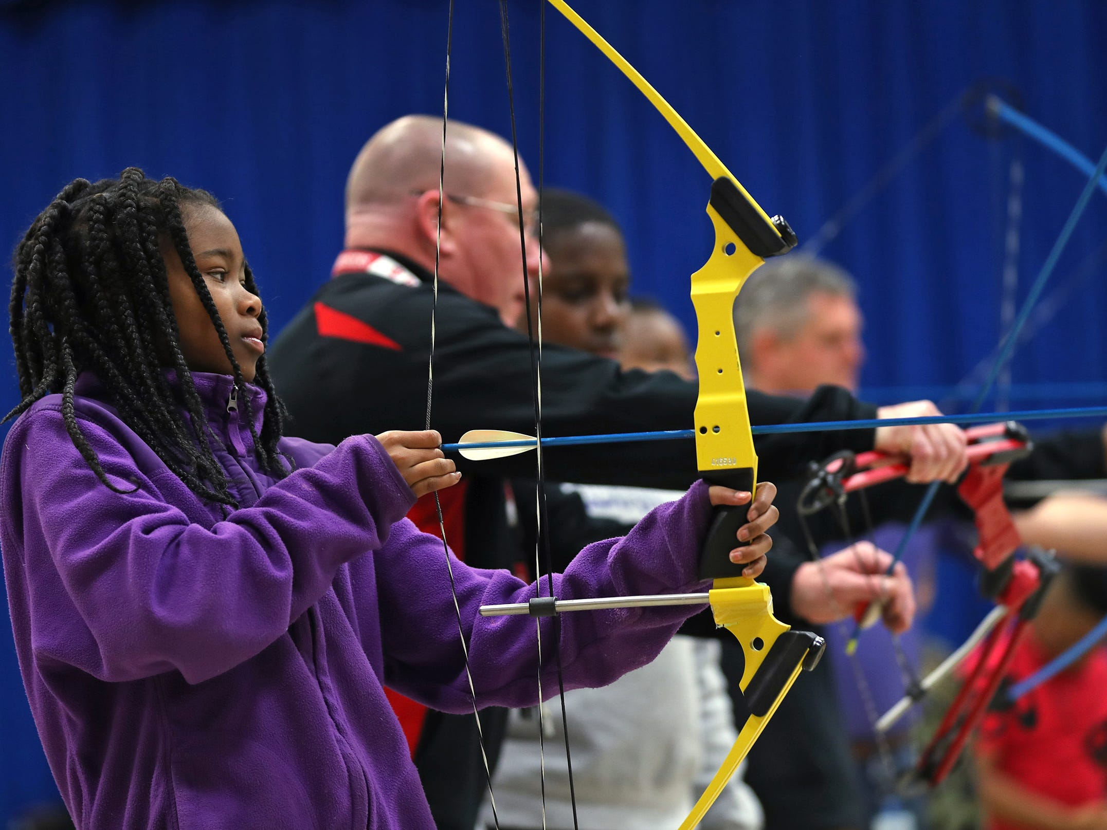 Brianna Smith, left, takes aim to shoot during archery class at Lew Wallace Elementary IPS 107, Thursday, Dec. 20, 2018.