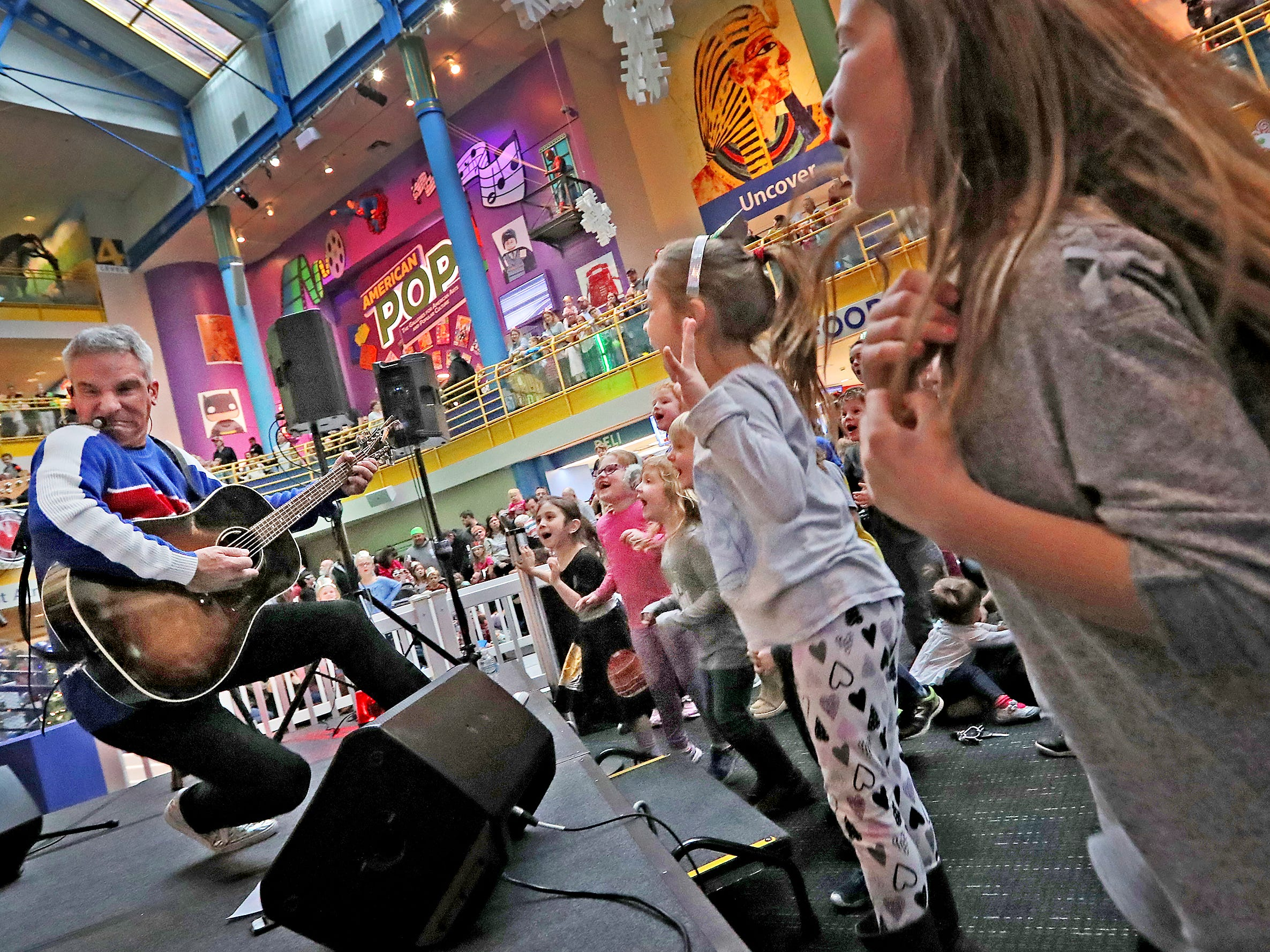 Zak Morgan,  left, pretends to fall as he and his group perform at the Countdown to noon celebration at the Children's Museum of Indianapolis, Monday, Dec. 31, 2018.