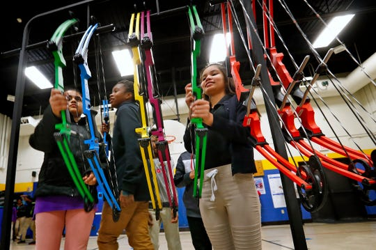 Ninoska Matamoros , right, and other students grab their bows for their turn to shoot during archery class at Lew Wallace Elementary IPS 107, Thursday, Dec. 20, 2018.