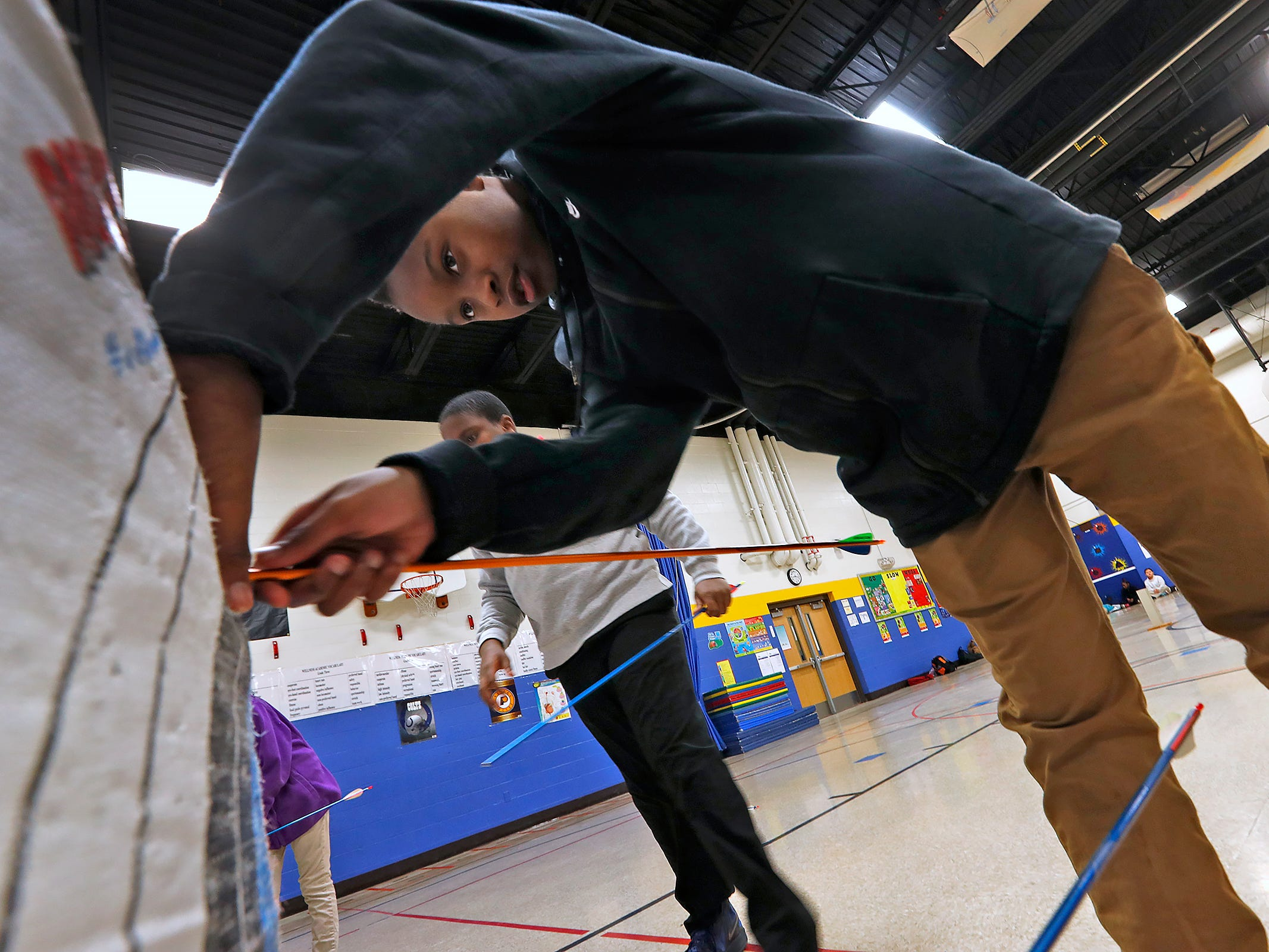 Aadian Richmond retrieves his arrow during archery class at Lew Wallace Elementary IPS 107, Thursday, Dec. 20, 2018.