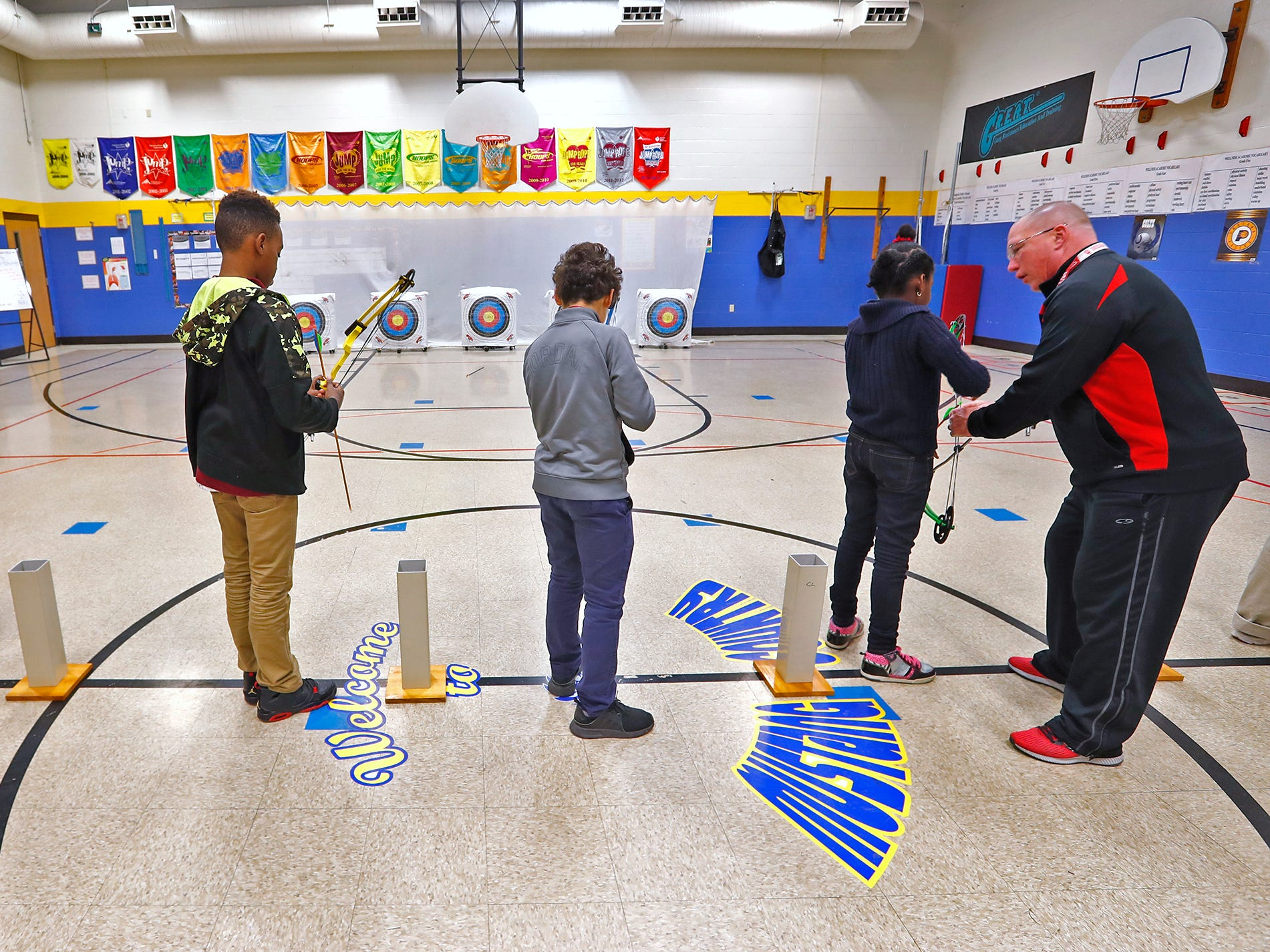 William Crawford, right, gives instruction to students ready to shoot during archery class at Lew Wallace Elementary IPS 107, Thursday, Dec. 20, 2018.