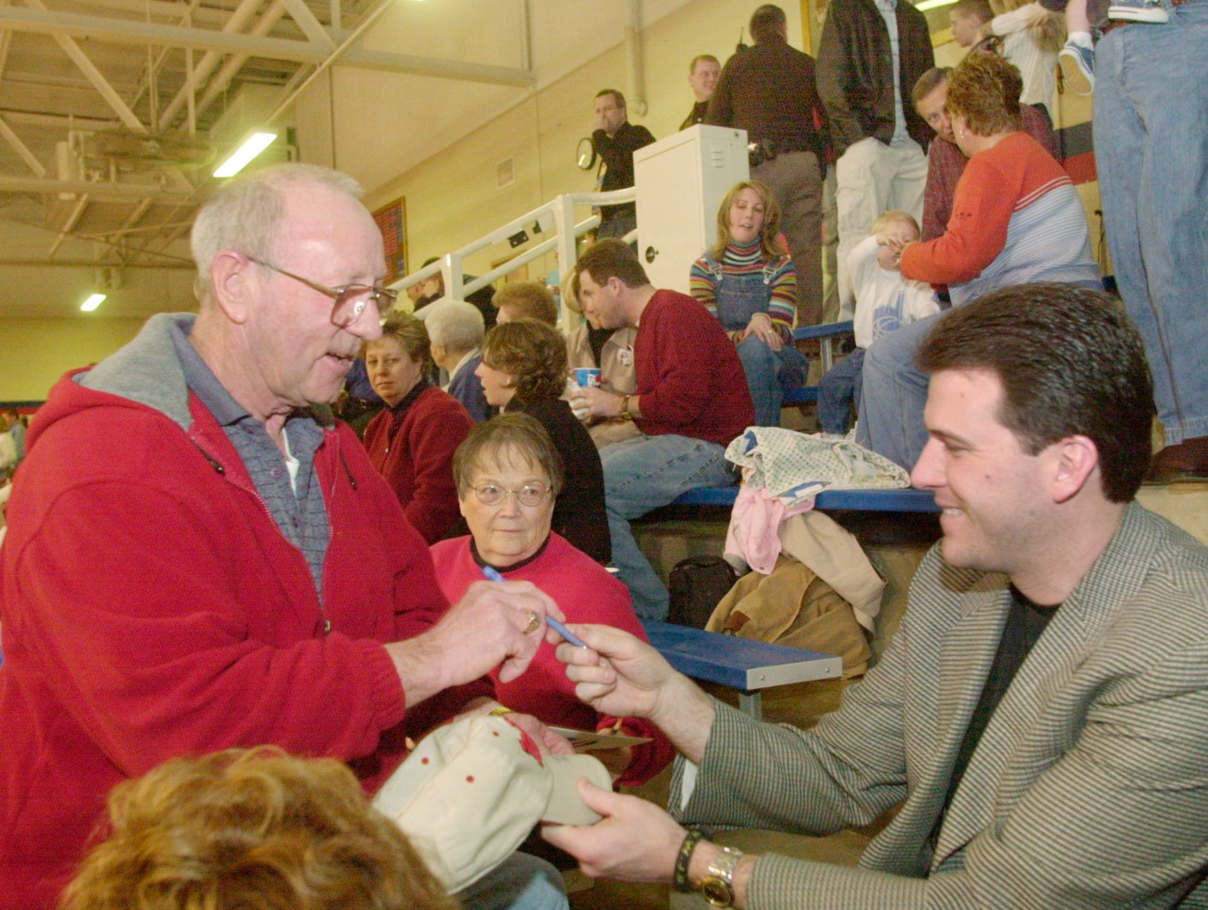 Trafalgar resident Vernon  Peavey (left) gets an autograph from University of Iowa Coach Steve Alford who was at the game with Indian Creek hosting Waldron.  Indian Creek's J.R. Angle (a senior) will play for Alford next year.