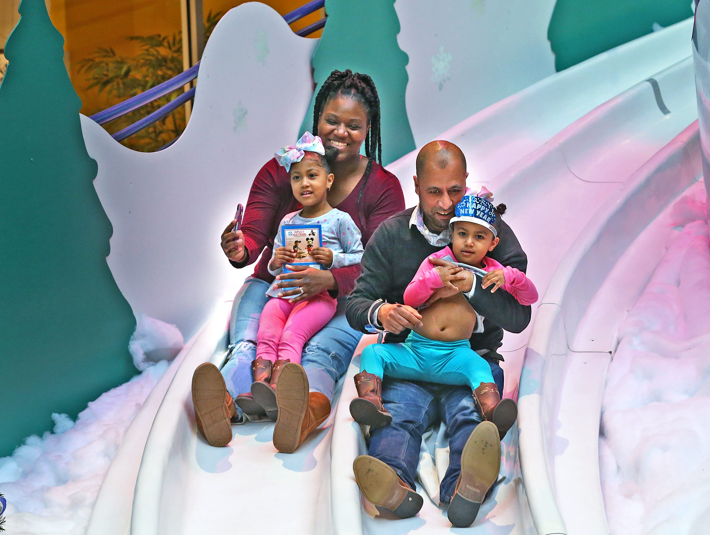 Lucy Payne, hold Aysha Labbaoui, and Abdul Labbaoui holding Amina Payne slide down the slide at the Countdown to noon celebration at the Children's Museum of Indianapolis, Monday, Dec. 31, 2018.