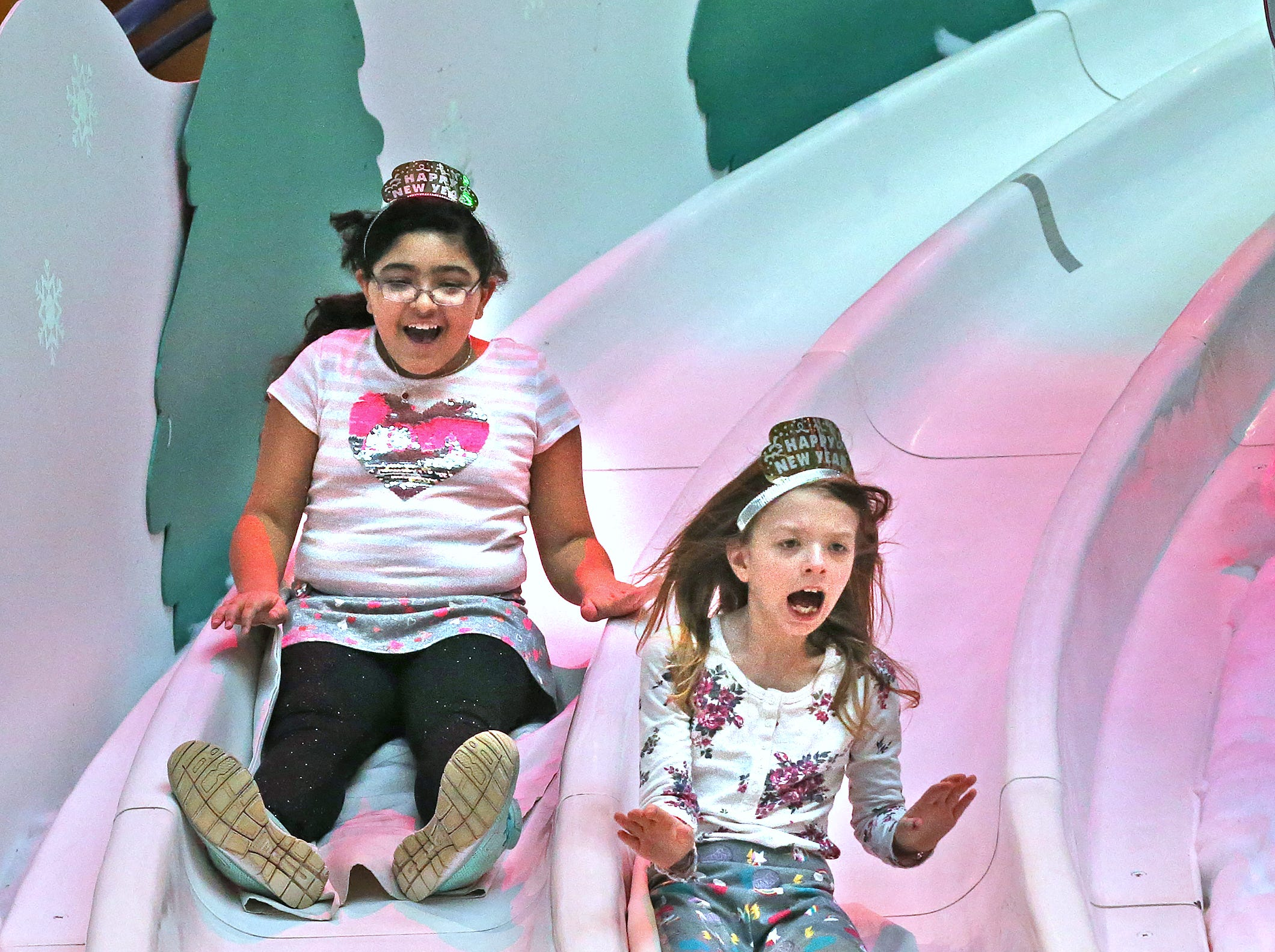 Eliora Coin, left, and Emily Crawford fly down the slide at the Countdown to noon celebration at the Children's Museum of Indianapolis, Monday, Dec. 31, 2018.