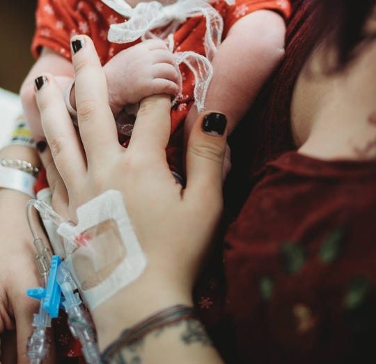 Krysta Davis holds hands with her newborn daughter.