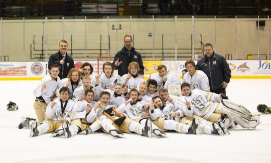 Howell's hockey team celebrates after winning the MacInnes Holiday Classic in Houghton.