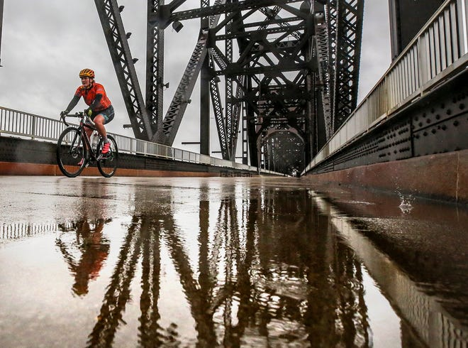 A cyclist crosses the Big Four Pedestrian Bridge Monday afternoon as rain showers boosted 2018 over the top to become Louisville's wettest year on record..December 31, 2018