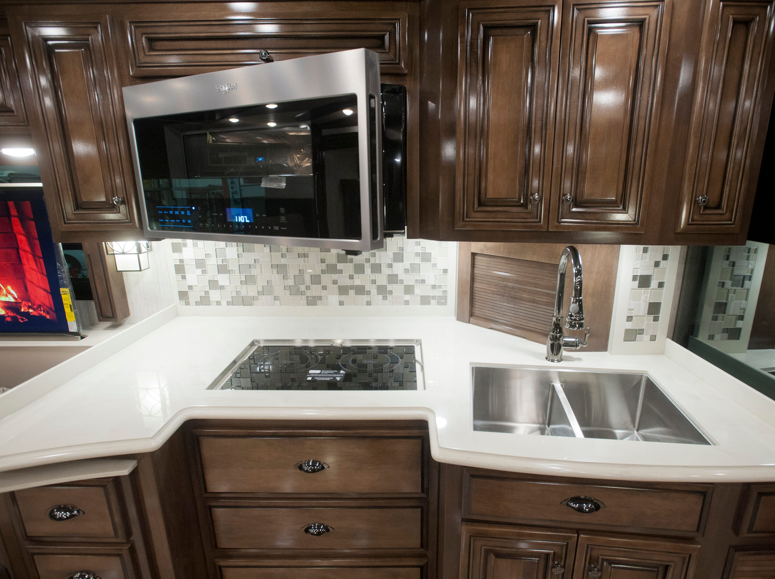 The kitchen with an induction stove top, a combination convection and microwave oven, and a steel double-sink.