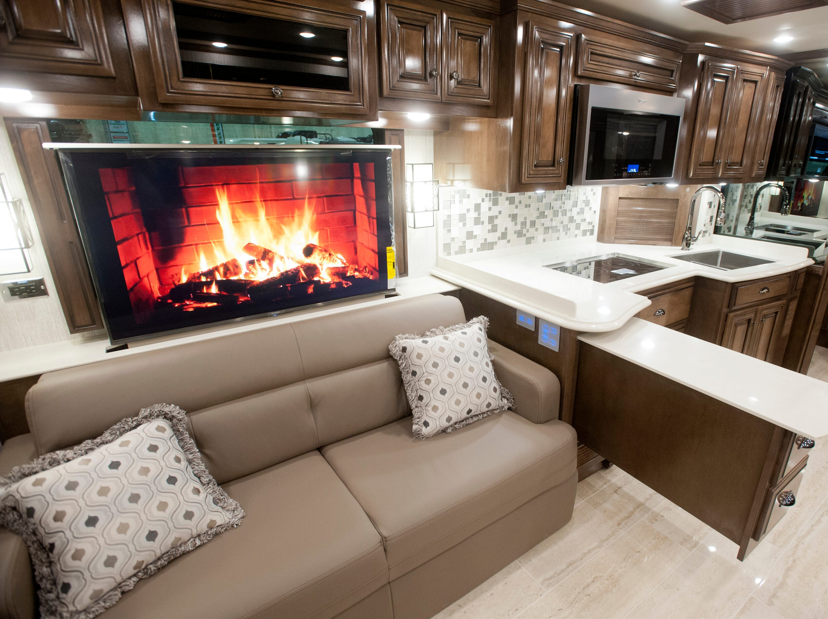 A television above one of the living room couches plays a video of a fireplace. At right is the coach's kitchen area.11 December 2018