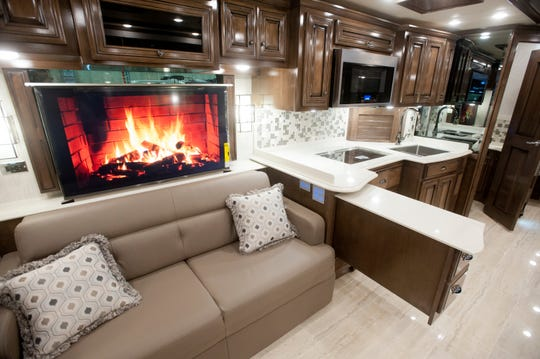 A television above one of the living room couches plays a video of a fireplace. At right is the coach's kitchen area.